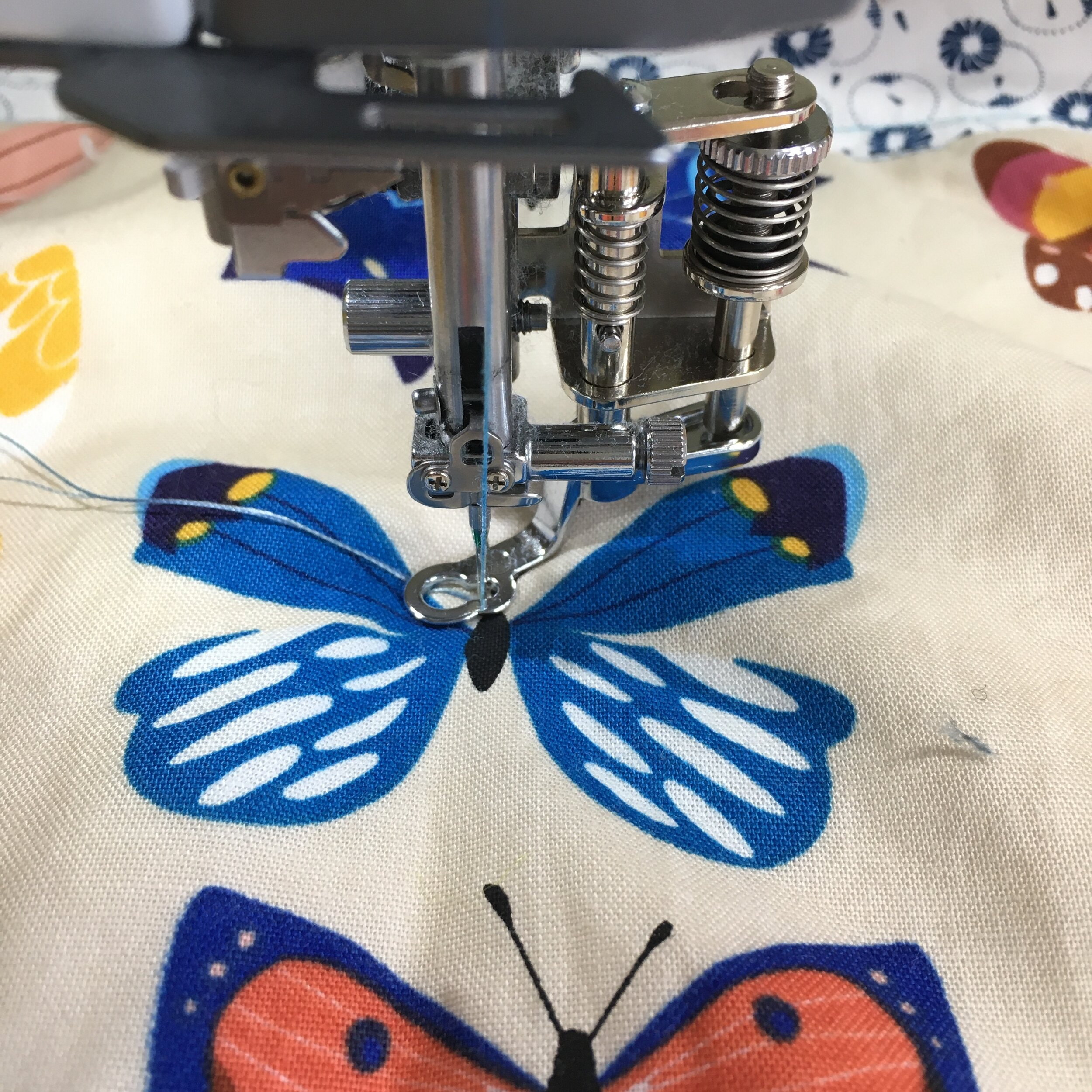 Bobbin thread has been pulled up from the back of the quilt.  Needle is down, reading to start quilting