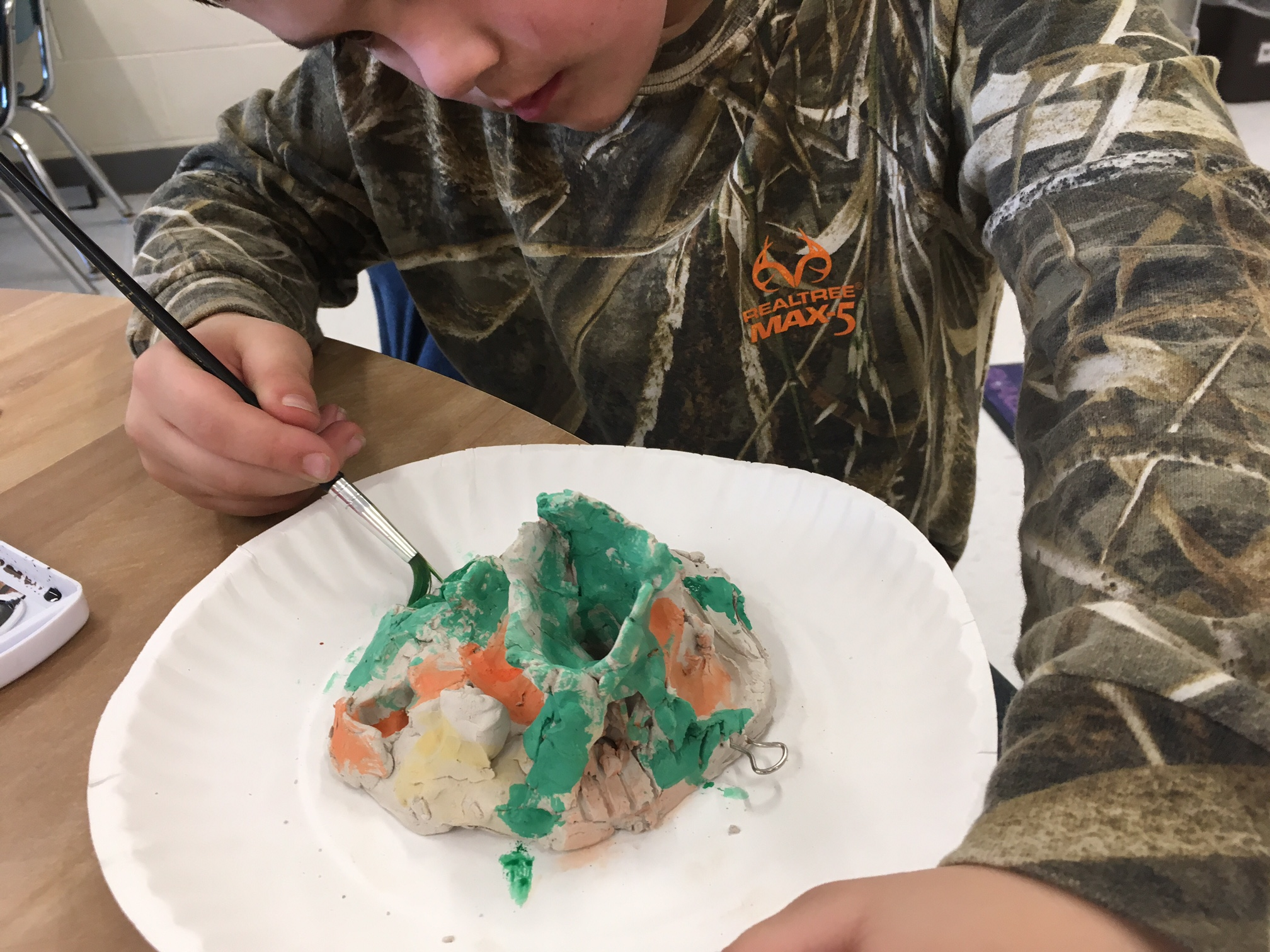 Here is one Kindergartener in Miss Cara's class painting his planet. He had a huge volcano and had a long river of lava.