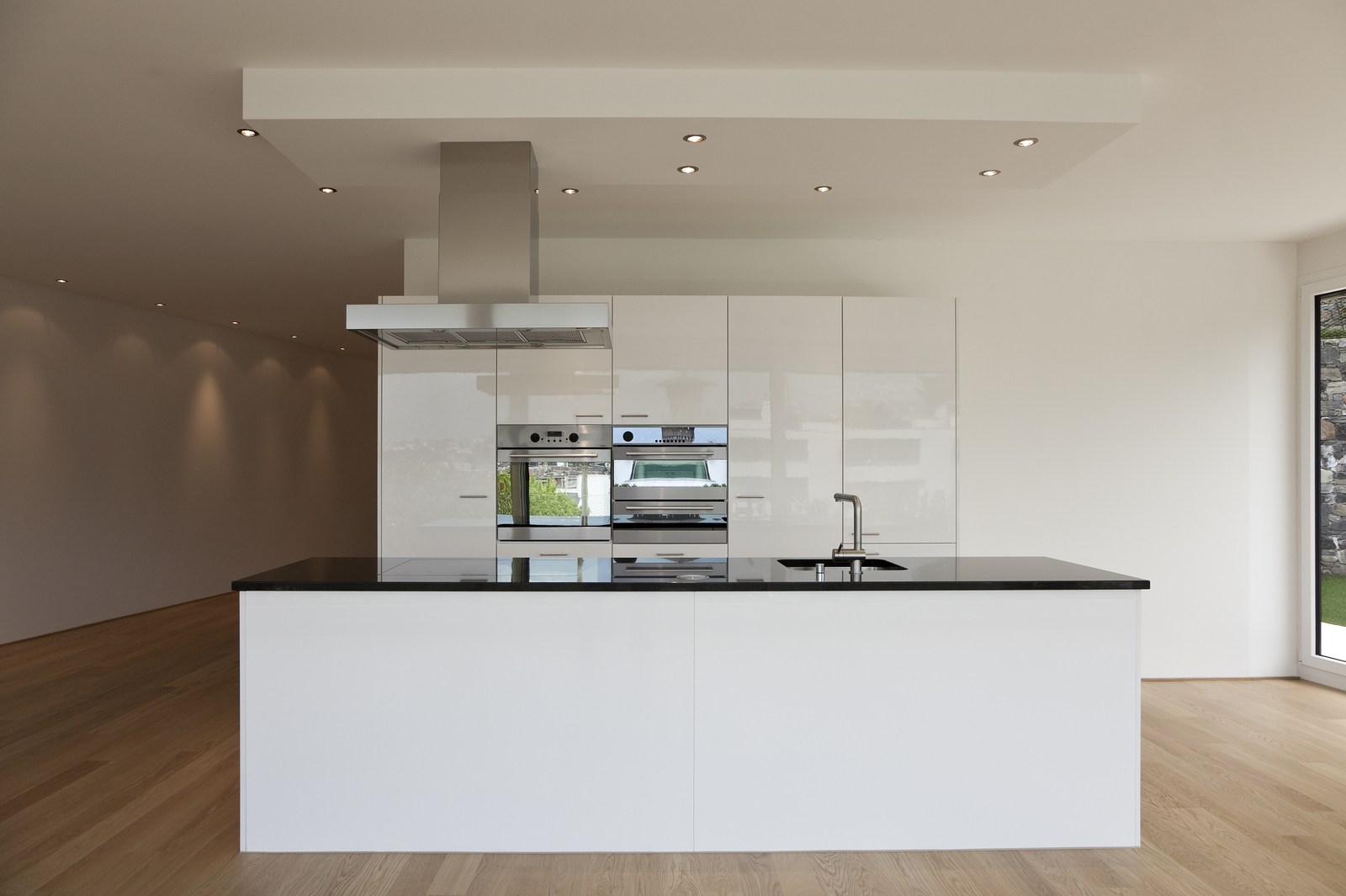 """Condo Kitchen  -  Combination of lacquered and low sheen cabinetry, built-in fridge and ovens, polished chrome plumbing fixtures and appliances, built-in cooktop flush in solid black engineered stone countertop. White oiled 5"""" wide oak plank floor. Polished chrome cabinet handles."""