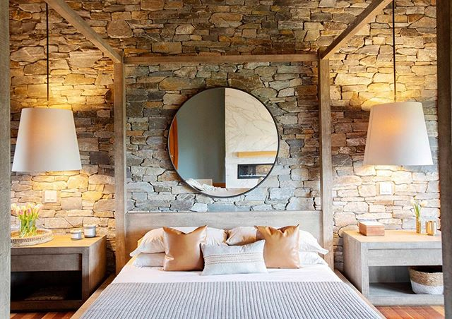 This giant canopy bed perfectly frames decor against the textural stone wall and helps cozy up the large master suite at our recent Naramata project. #k2stonequarries #naramata #winecountryliving #restorationhardware 📸 @pineconecamp