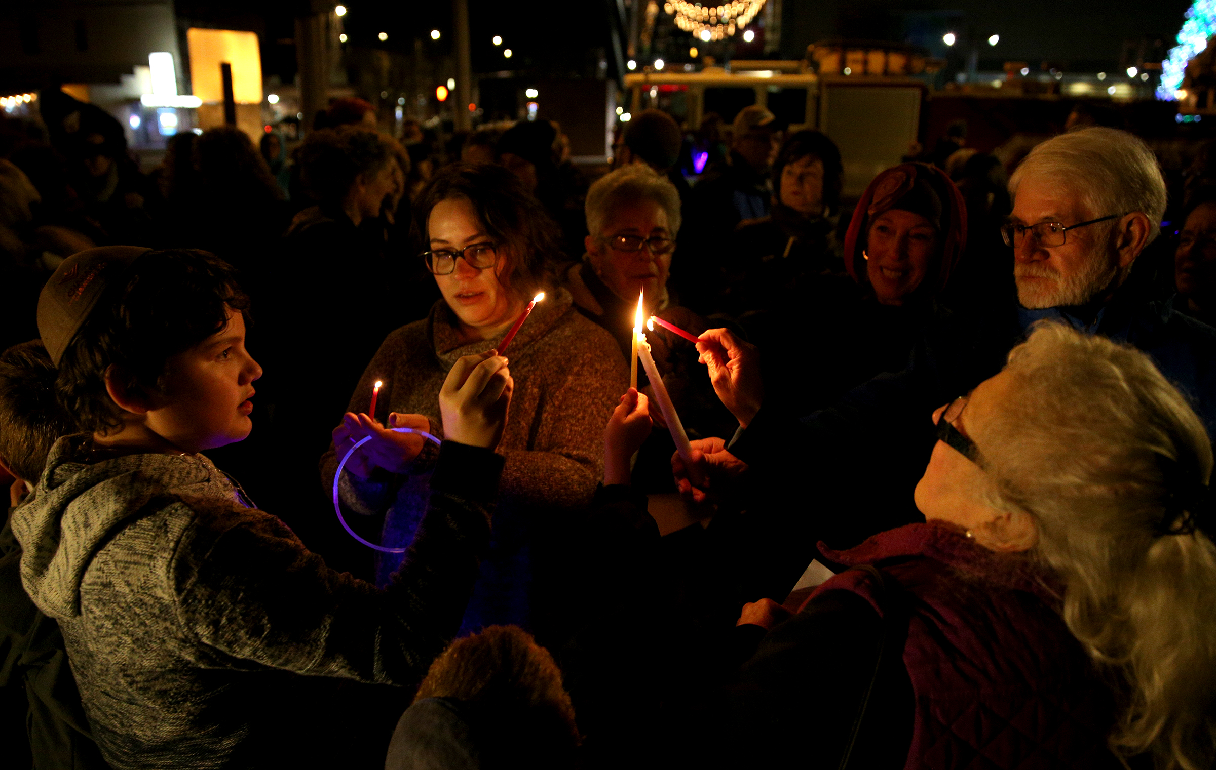 Attendees of a menorah lighting, hosted by the Chabab Center for Jewish Life, light candles on the first day of Hanukkah at Mirror Park in downtown Salem, Ore. on Sunday, Dec. 2, 2018. The candles were lit to show solidarity with the Jewish community in Pittsburgh.
