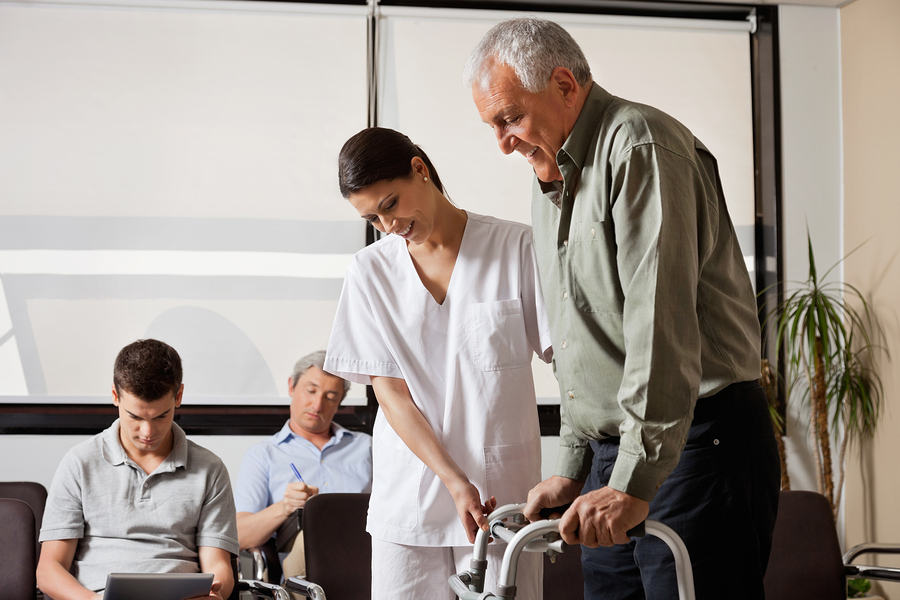 Nurse assisting senior with mobility aid