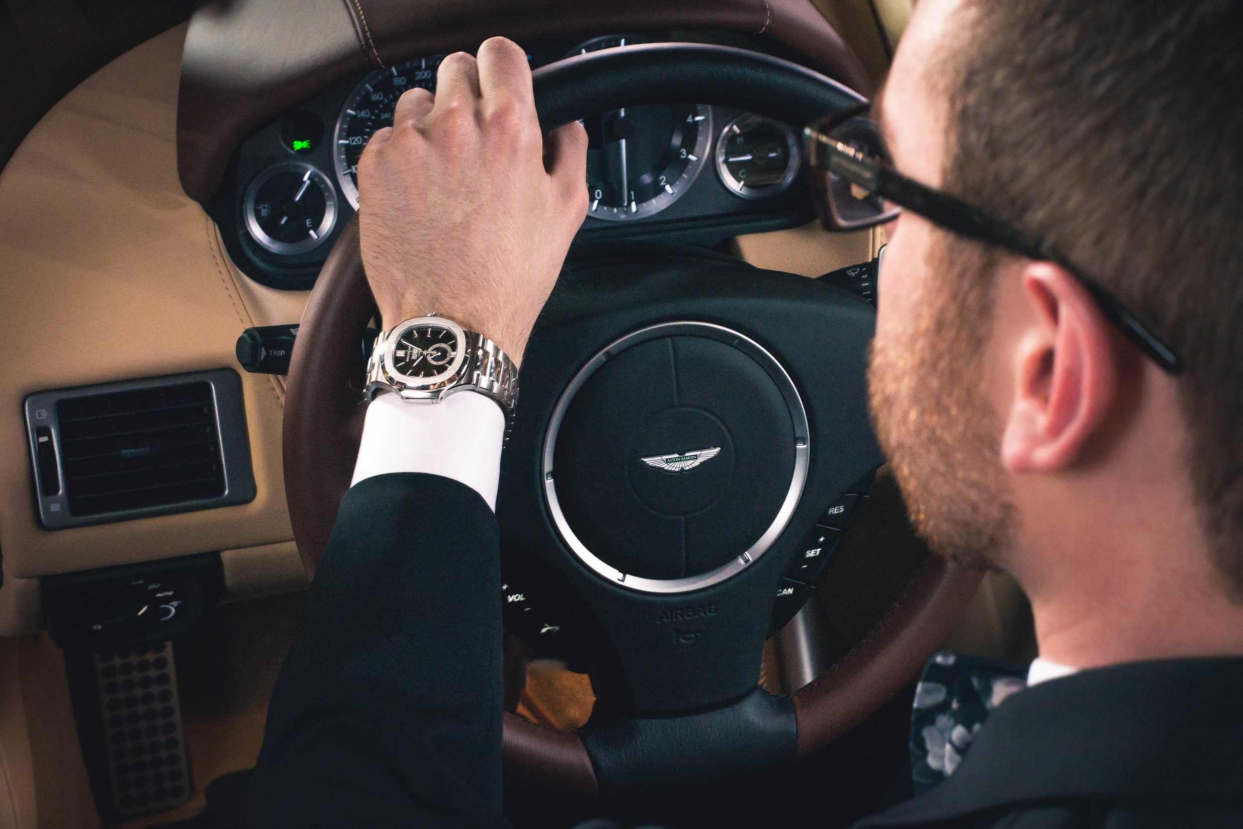 Watch: Patek Philippe Nautilus, Tuxedo: Armani Collezioni, Shirt: Ledbury, Tie: The Tie Bar, Shoes: Crosby Square, Glasses: Burberry, Car: 2014 Aston Martin DB9 Volante(courtesy Foreign Cars Italia), Photo: Alec Hutchins Photography, Model: Noah Williams