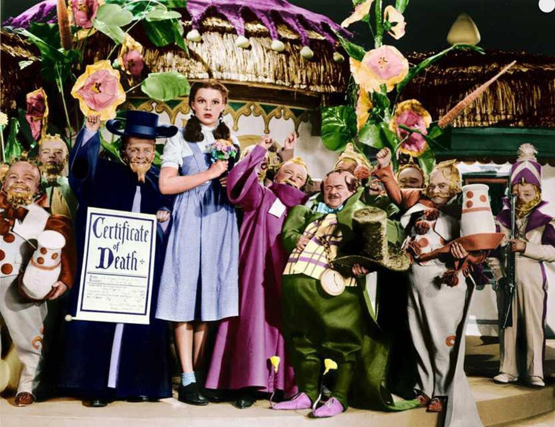 Judy Garland surrounded by The Munchkins.