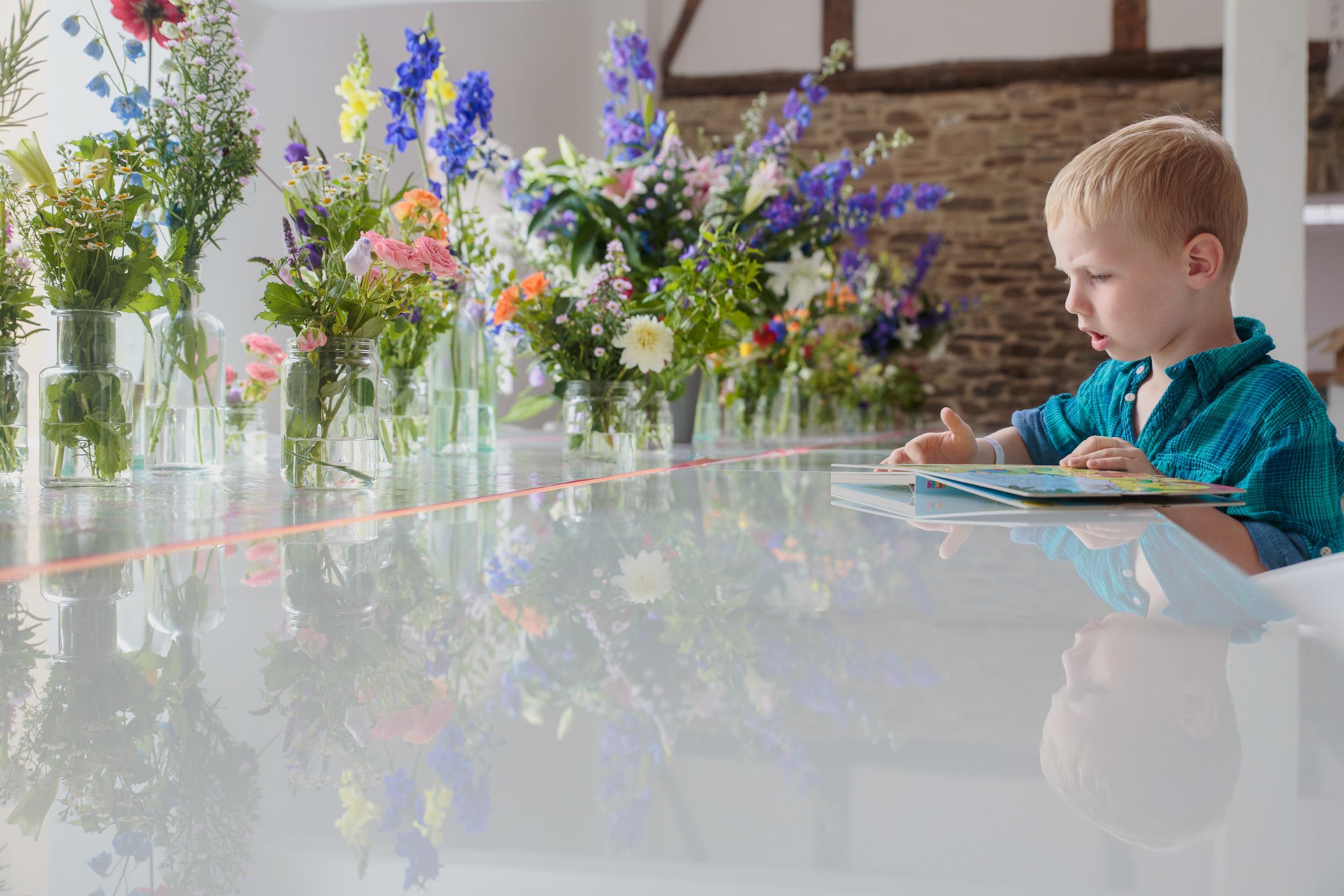 Karin en Vincent (woonachtig in het verre Uden, NL) kozen voor een huwelijk in de exotische Ardennen (Sechery) en bijpassende exotische Belgjes iso800 als fotografen. Met het hele gezin en een meute vrienden, familie en sympathisanten zetten ze een heel weekend lang de geweldige feestzaal op stelten. Kindje eest boek bij de tafel vol bloemen.