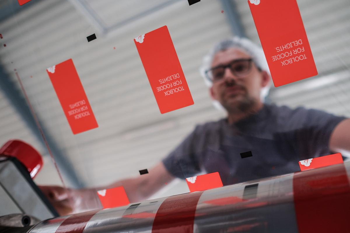 Onder een machine bij een producent van inpakplastic. / Under heavy machinery in a plastic factory. (Interni)