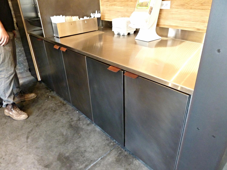 Patina'd steel cabinet doors, oak wall cladding