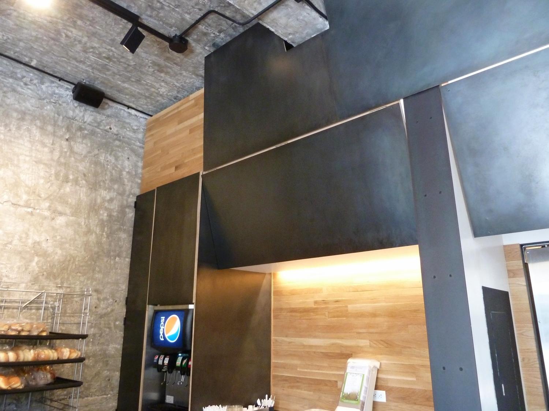 Patina'd steel menu board and doors, oak wall cladding