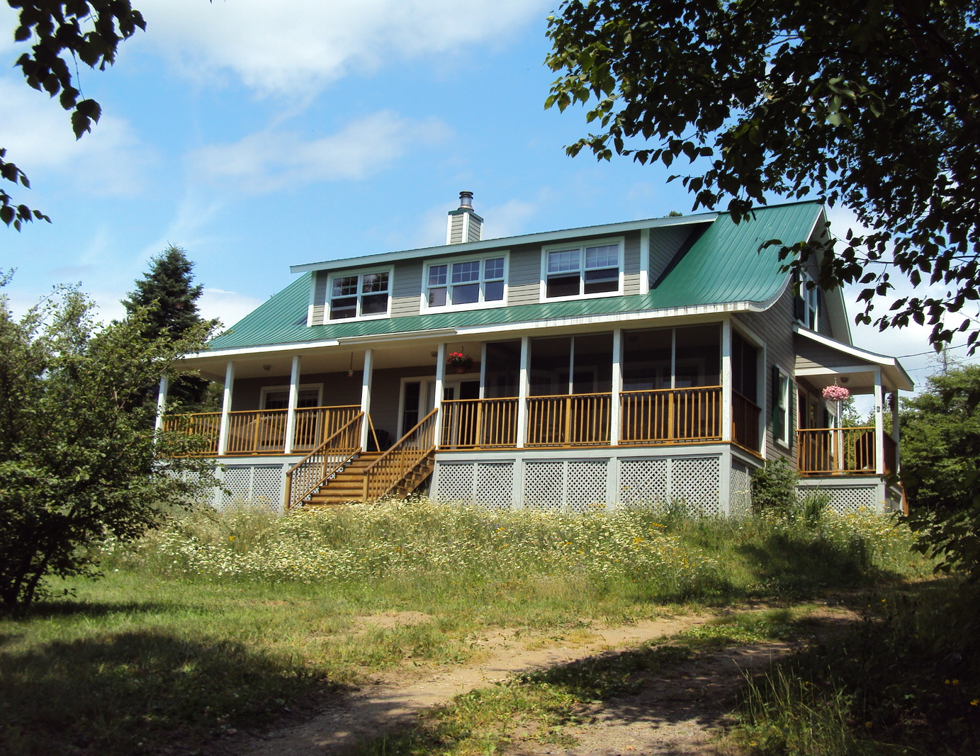 The house sits on the highest portion of the property, and has views of the Saguenay River, where it meets the St Lawrence. The front porch has a screened-in portion, to fend off the black flies in June.