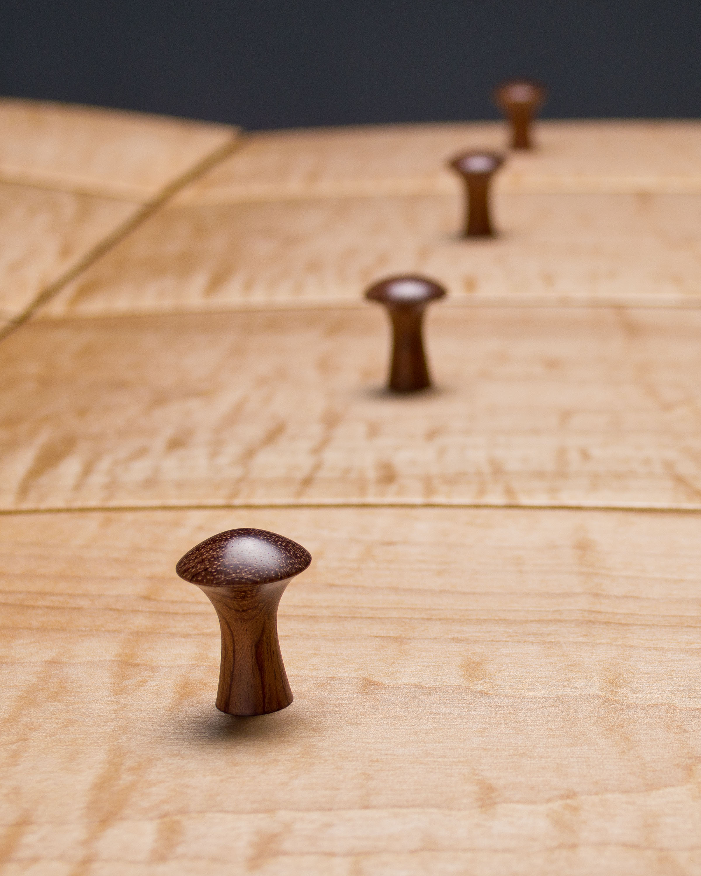 Bubinga was used for the turned knobs, which are secured to the drawer fronts with wedged through tenons.