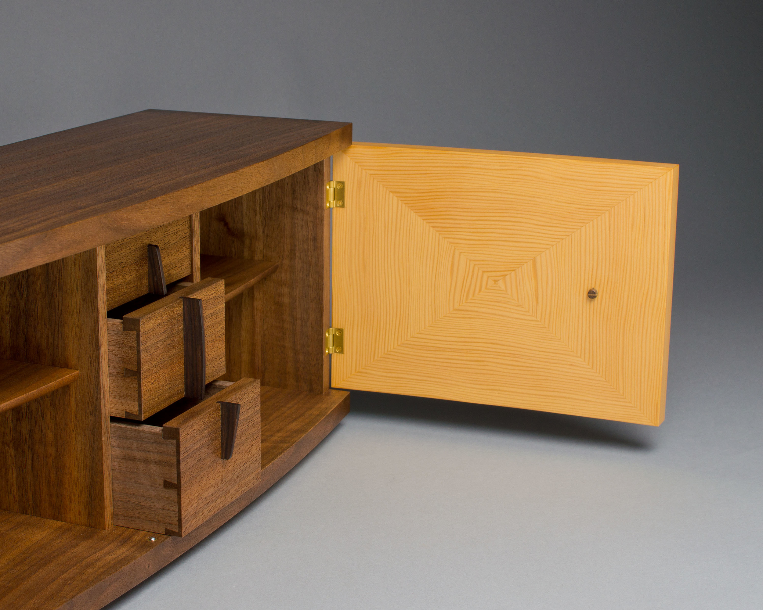 inside the cabinet is a column of three small dovetailed drawers