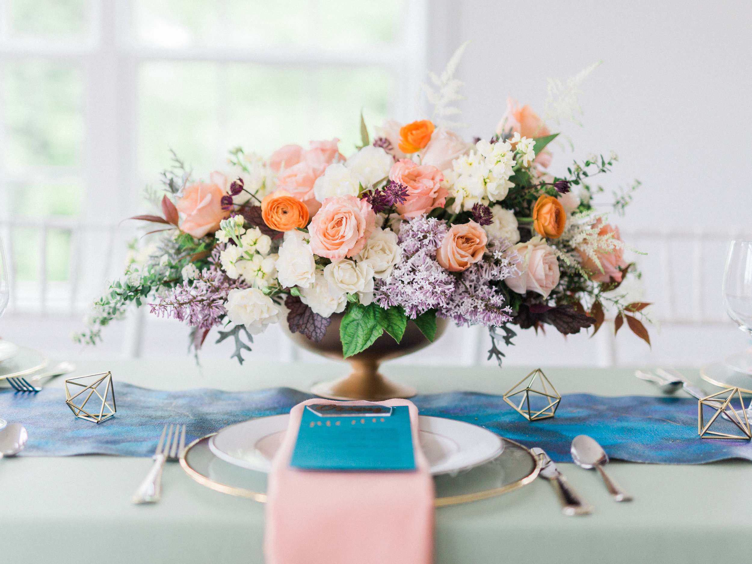 Amazing centerpiece with peach garden roses and purple lilac by Lark Floral