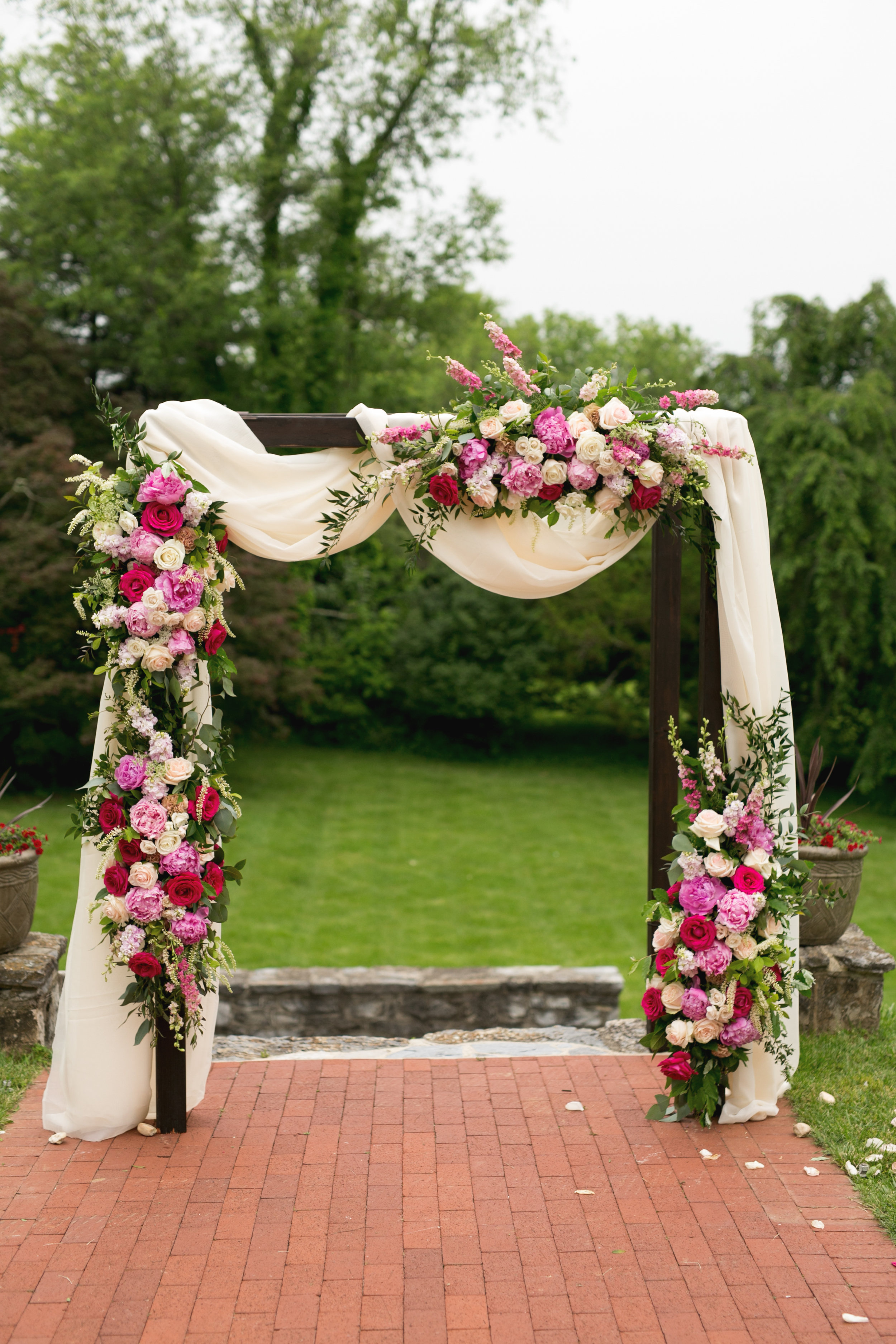 Wedding arch with lush pink flowers and draping by Lark Floral at Rosemont Manor in Berryville, VA