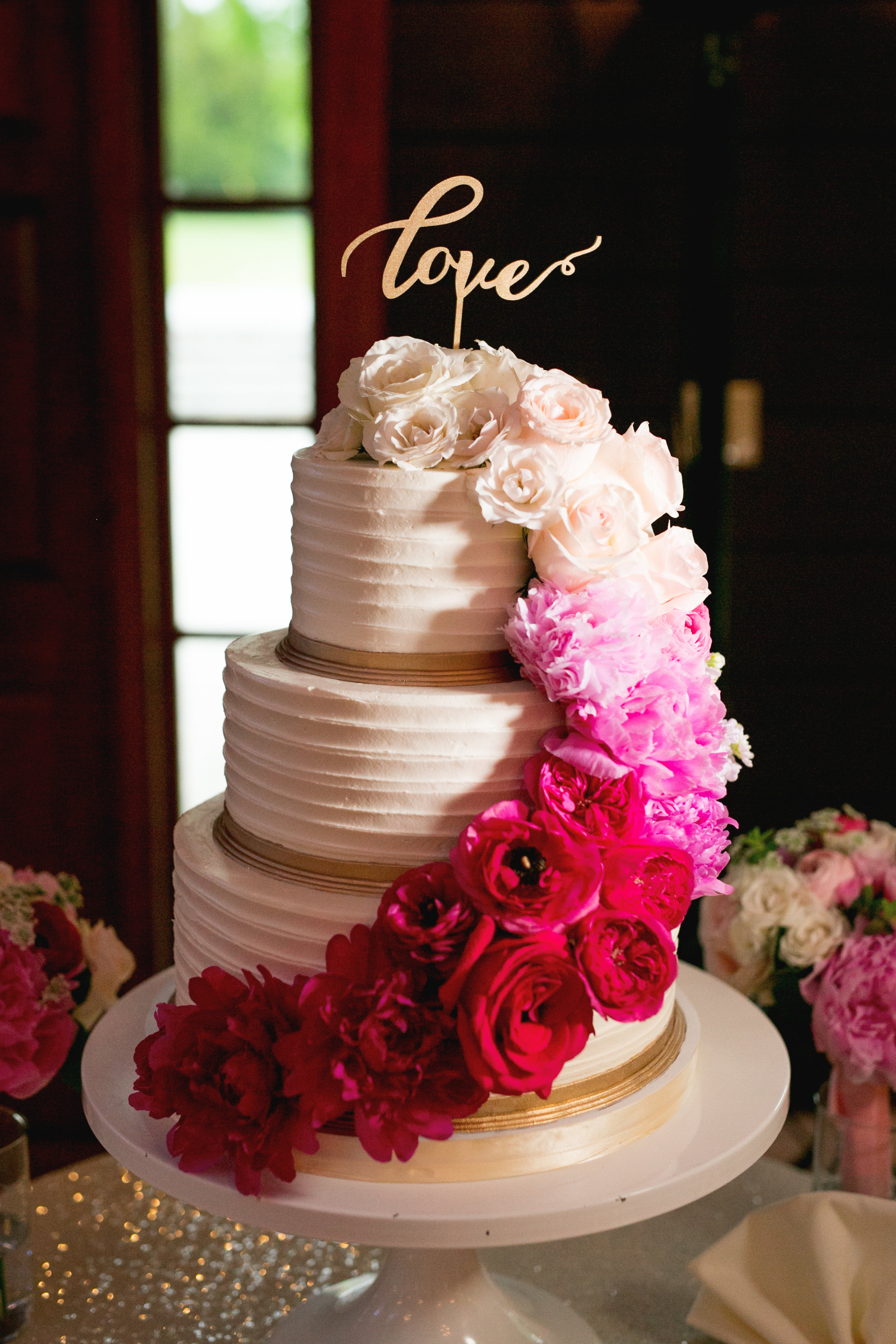 An ombre cascade of real flowers adorning the wedding cake was a showstopper!