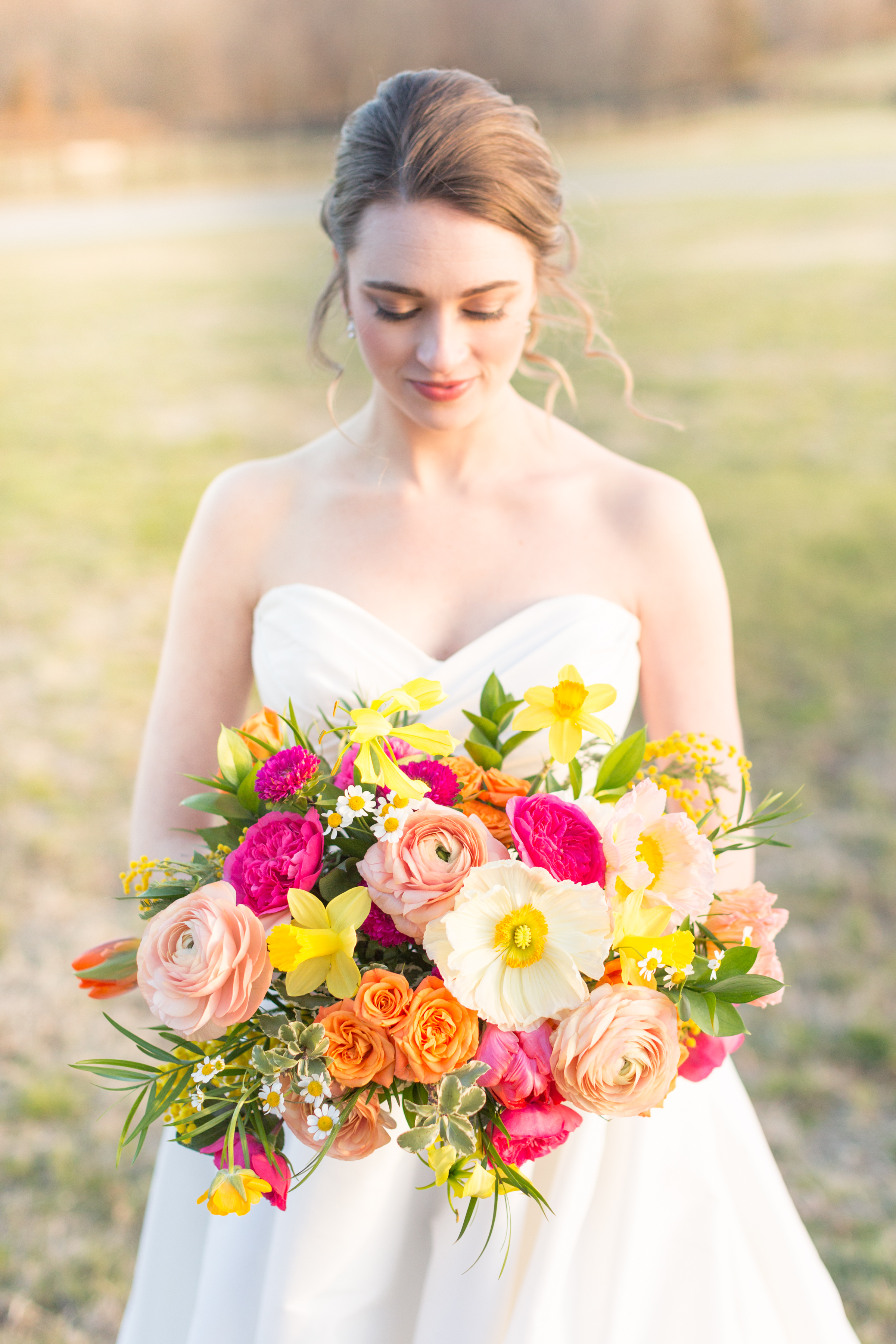 Spring bridal bouquet of daffodil, ranunculus, garden rose, tulips, gloriosa lily, mimosa