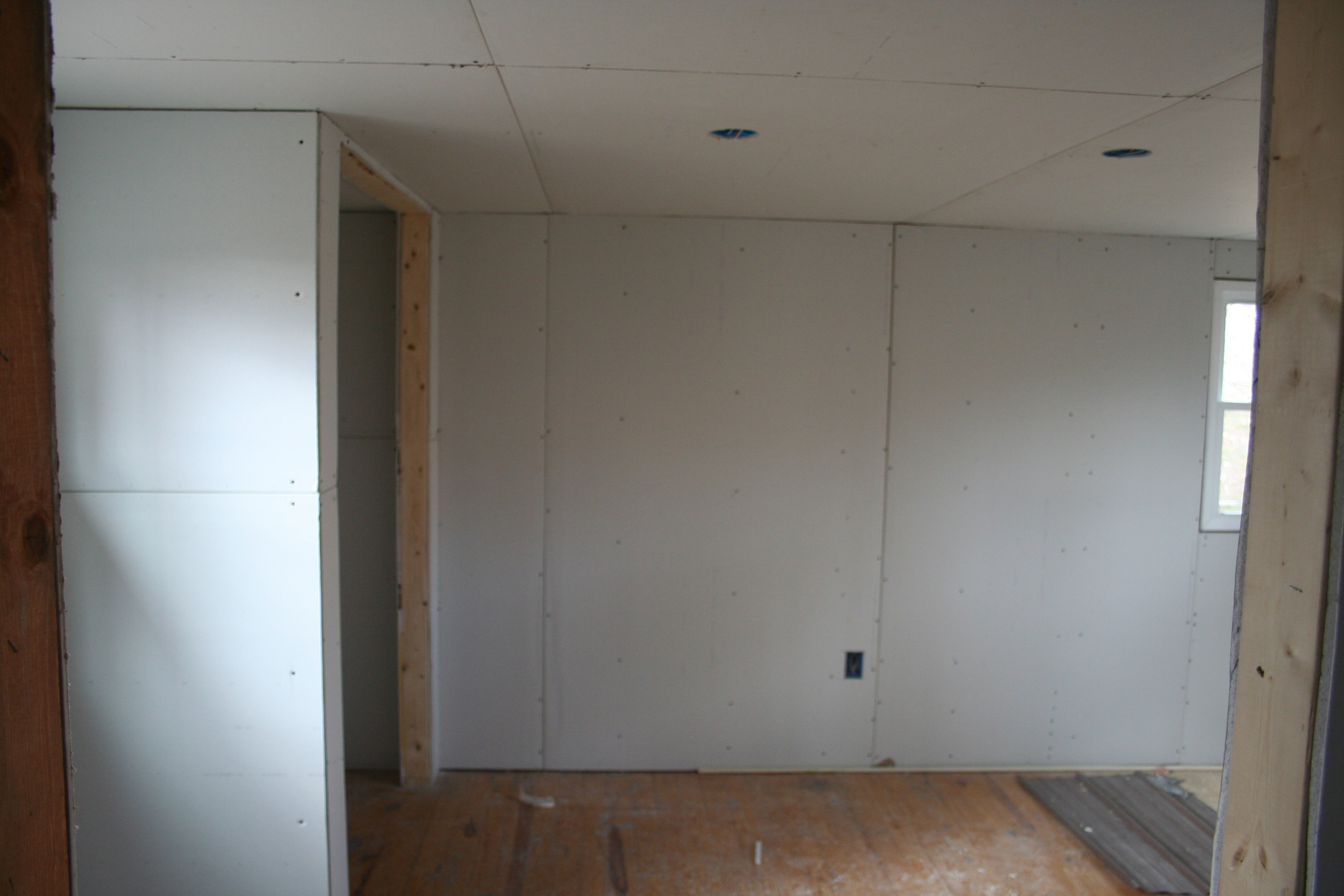 The view from the hallway into the bedroom. This is where the drywalling has begun!