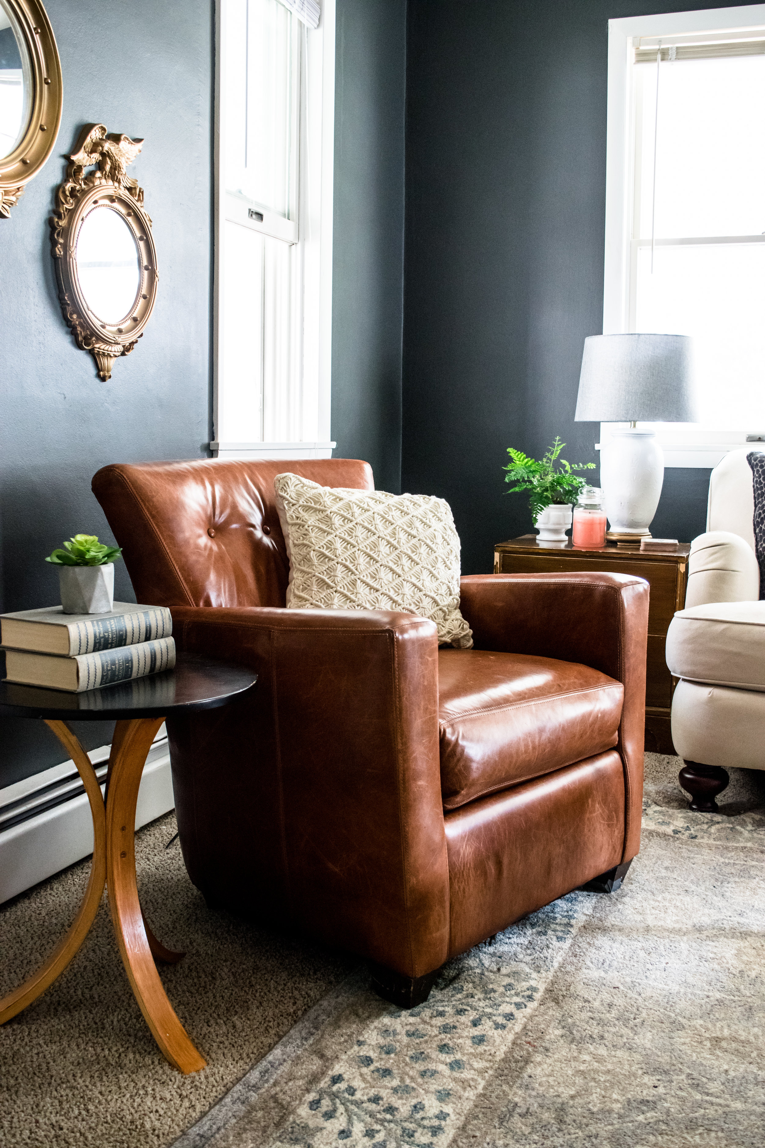Modern traditional country living room inspiration | English arm sofa, charles of london, french wingback chairs, distressed leather midcentury modern chair, black walls living room, grey persian rug, thrift store style