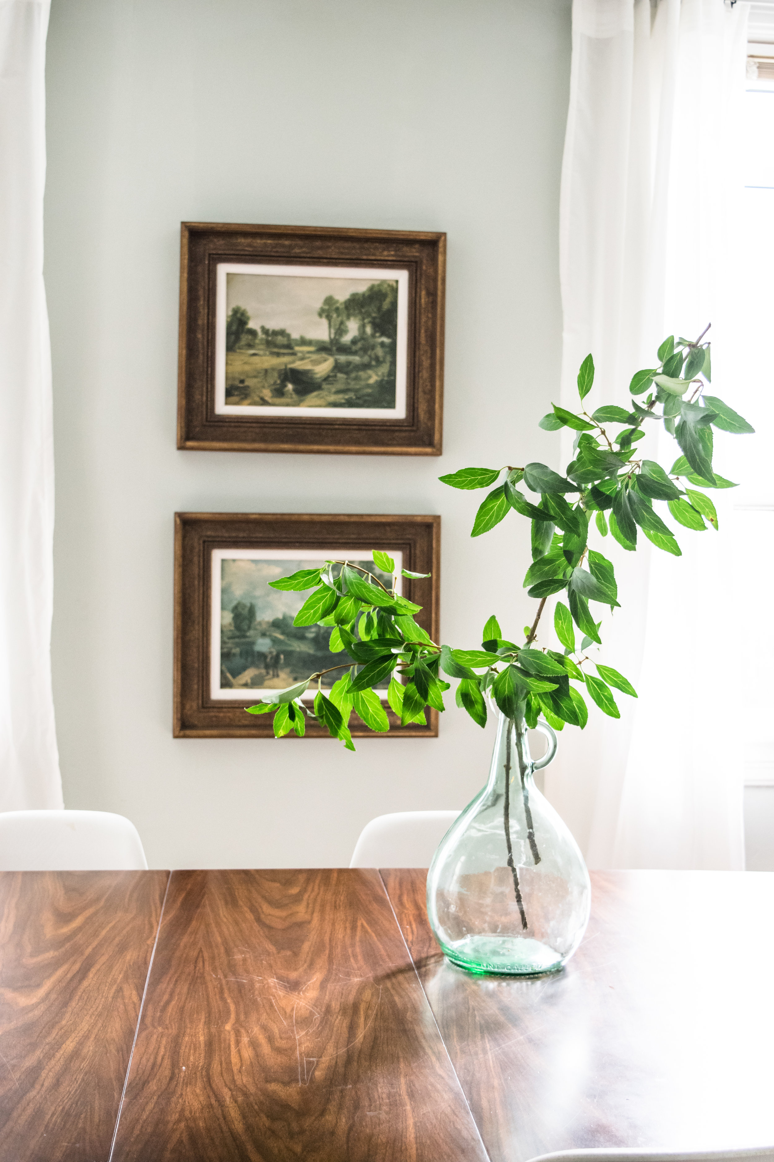 Modern meet antique dining room decor inspiration | antique piano, midcentury walnut dining table, white eames chairs, sherwin williams pearl gray walls, sherwin williams alabaster trim, antique oil painting reproductions, midcentury still life painting, sheepskin on piano bench