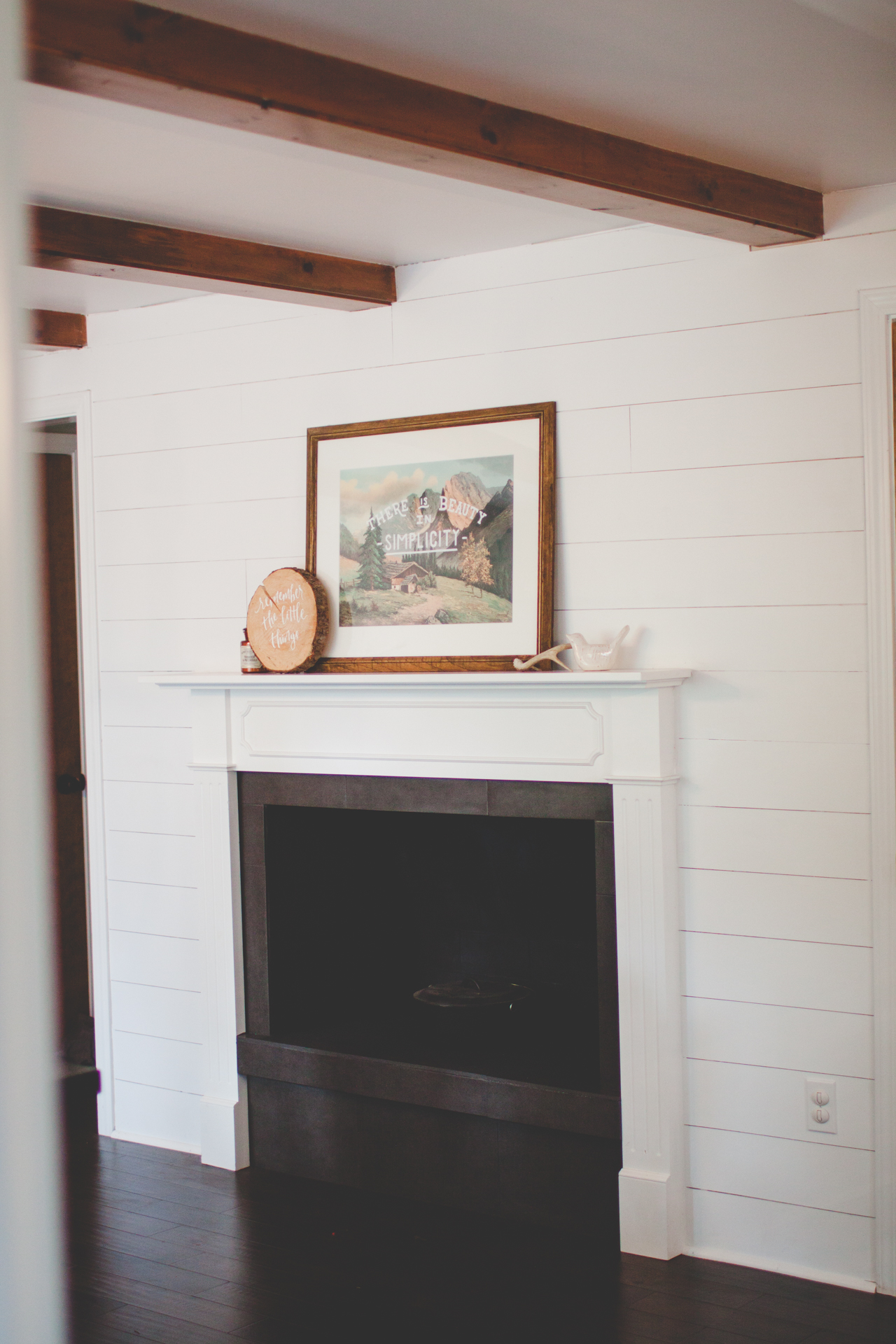AFTER: New mantle, painted fireplace, new tile, shiplap, floors.