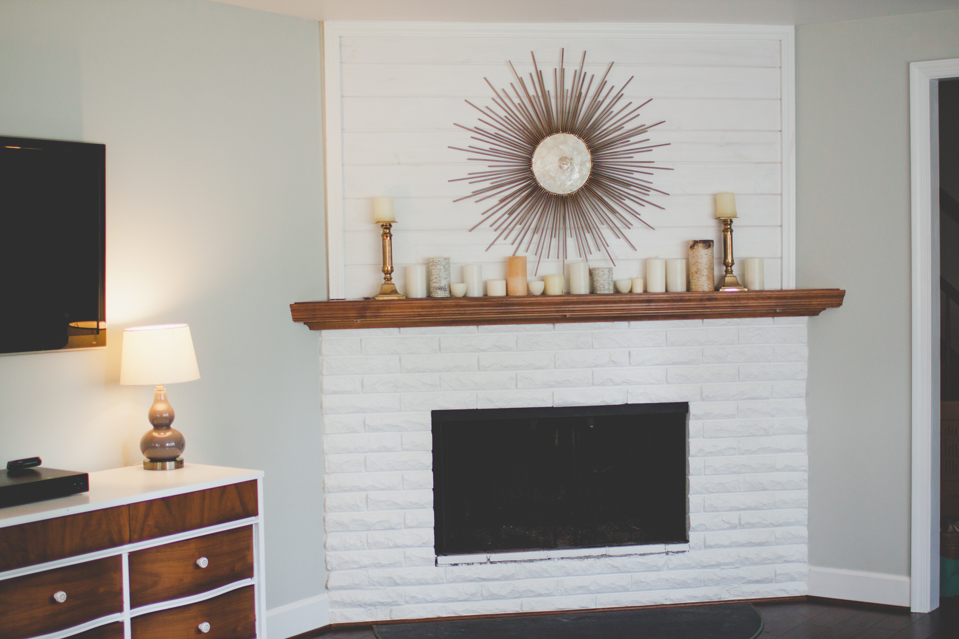 AFTER: One of my favorite transformations! Removed the old giant mirror, added white washed shiplap, painted the dank 70s tile white, painted the inside of the fireplace and hardware.