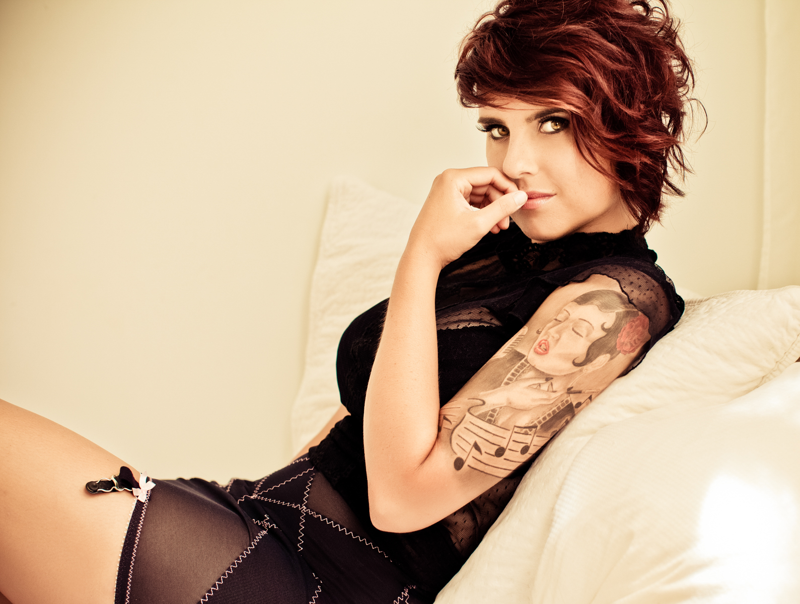 Redhead woman with sleeve tattoo in black lingerie