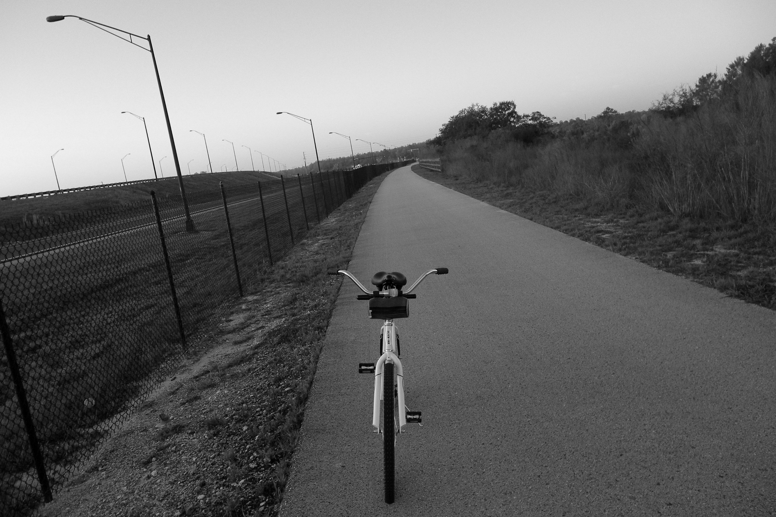 a black and white photo of a bicycle going down a road