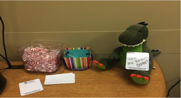 a table with peppermints and a stuffed dinosaur on top.