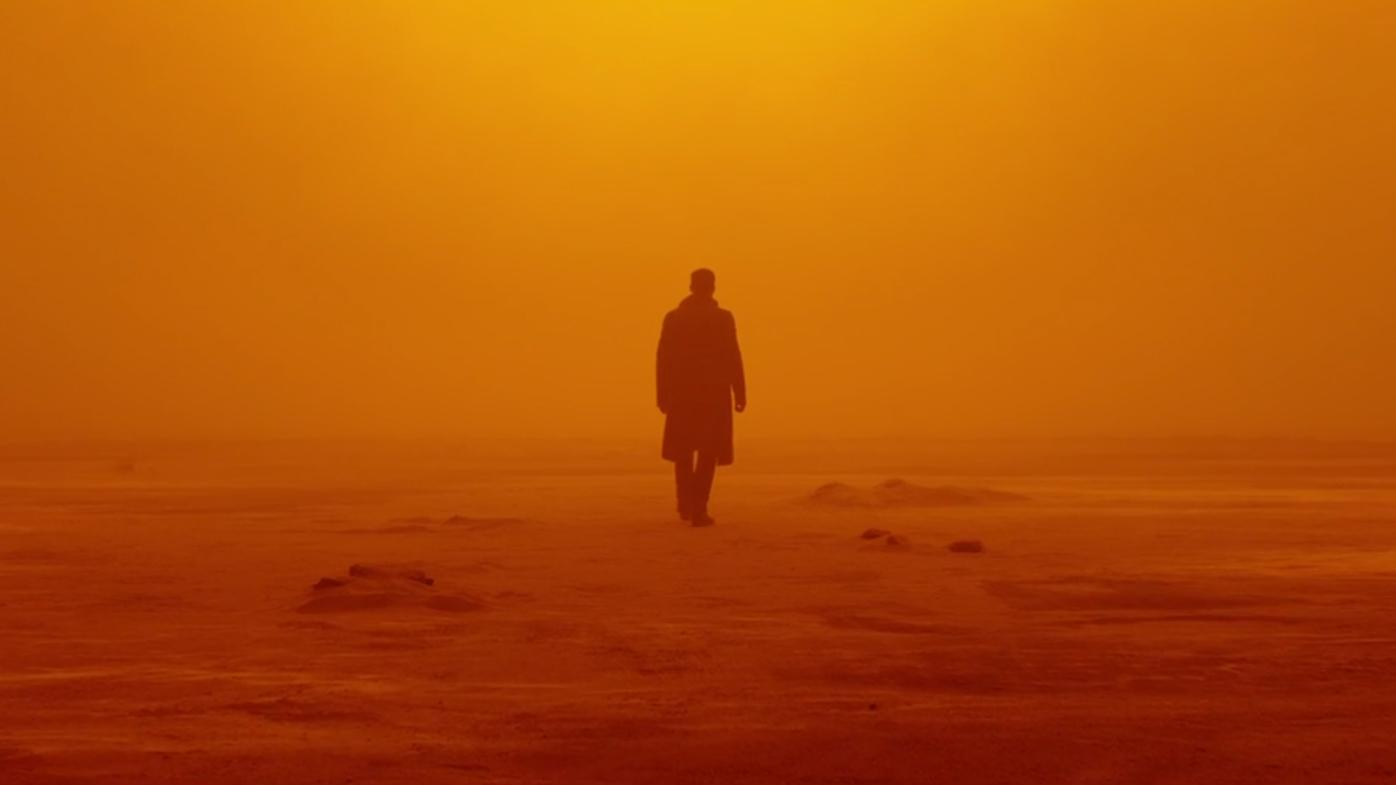 an image from the movie Blade Runner, where there is a man standing in orange/yellow light.