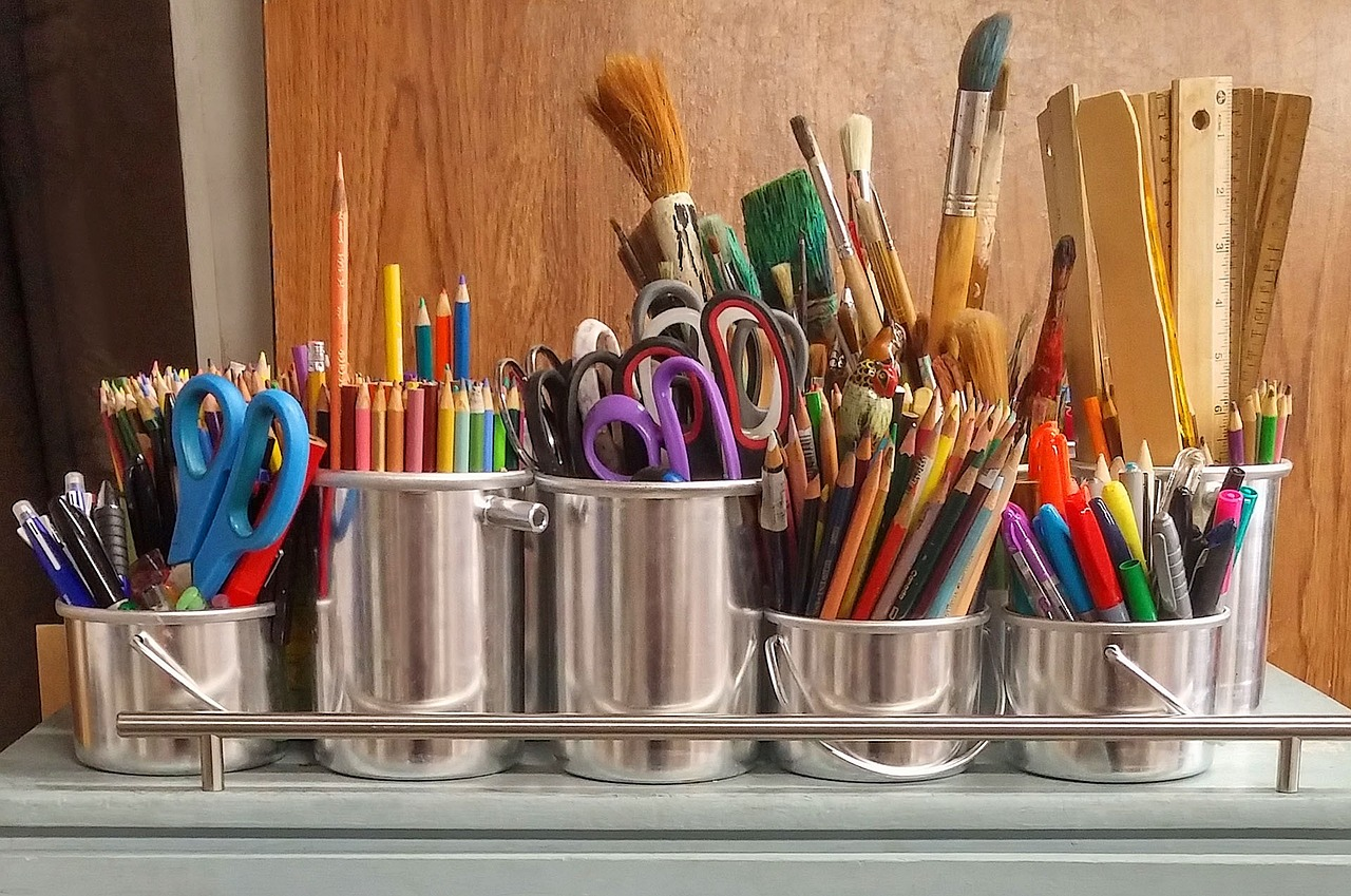 silver cans filled with school supplies, such as scissors, colored pencils, paint brushes and rulers.