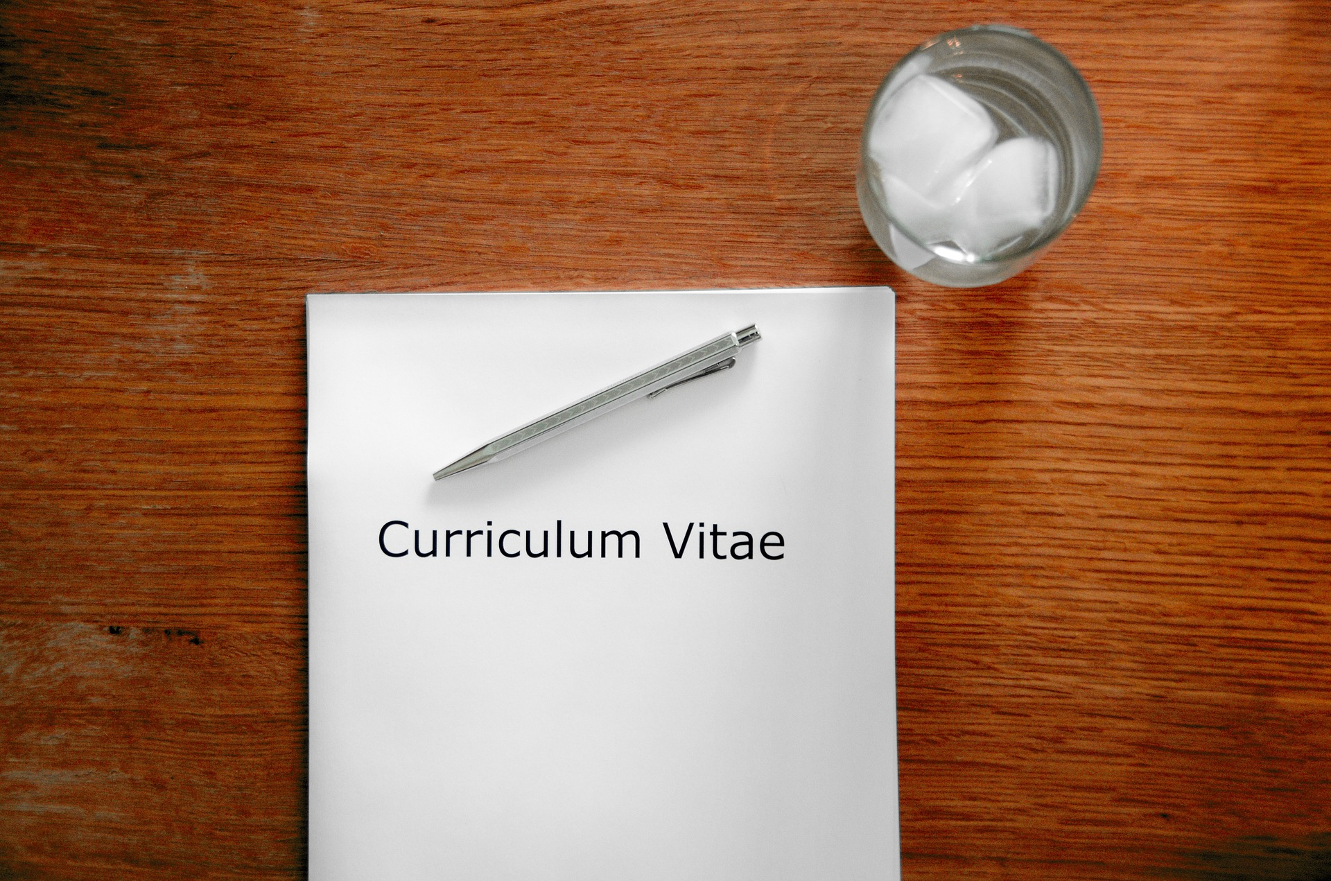 """a white sheet of paper that reads """"Curriculum Vitae,"""" with a pen on top and a water glass next to it."""