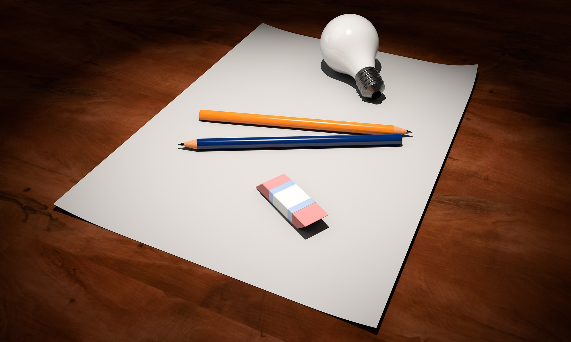 two pencils, an eraser and a light bulb on top of a blank piece of paper.