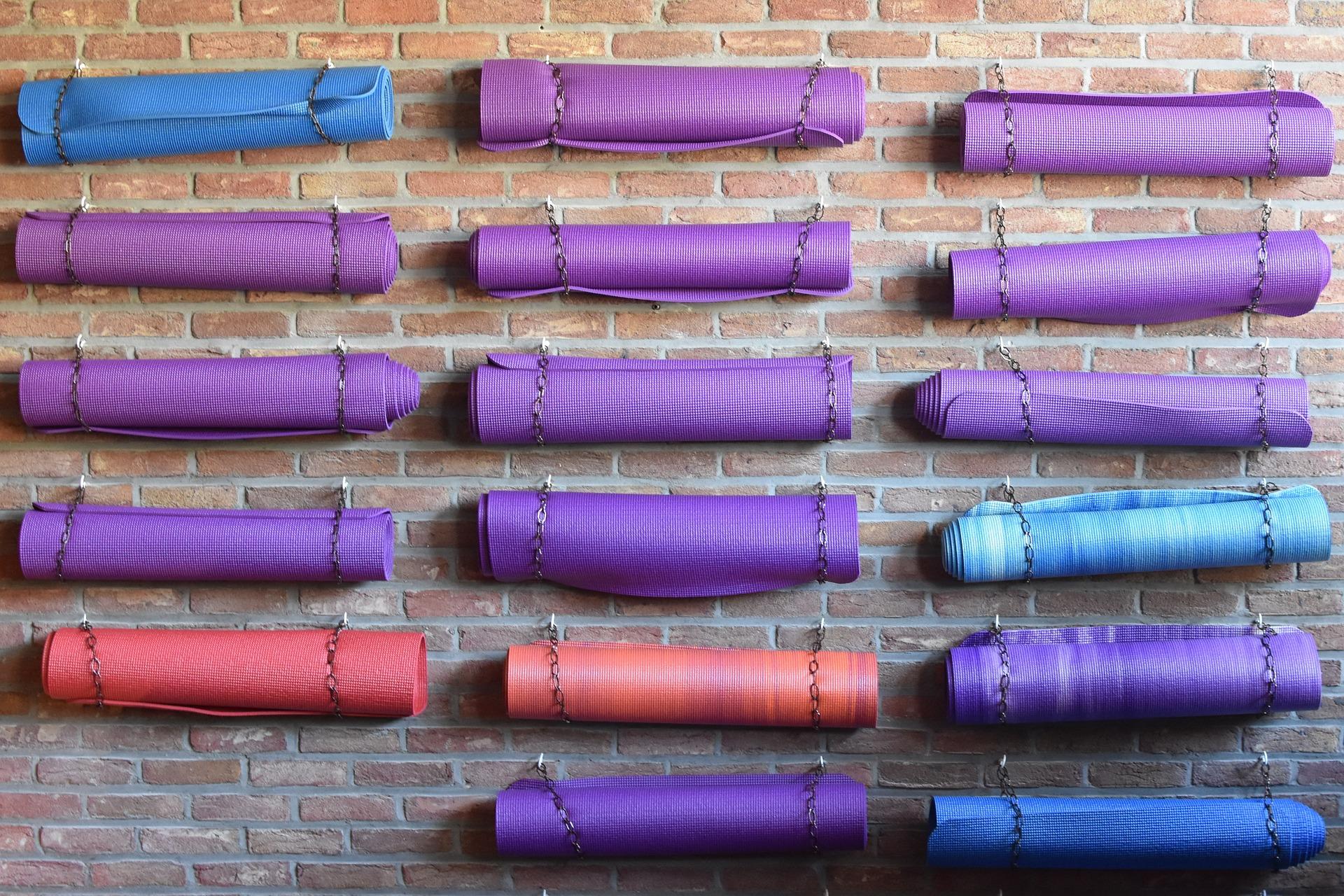 a brick wall with hanging yoga mats.