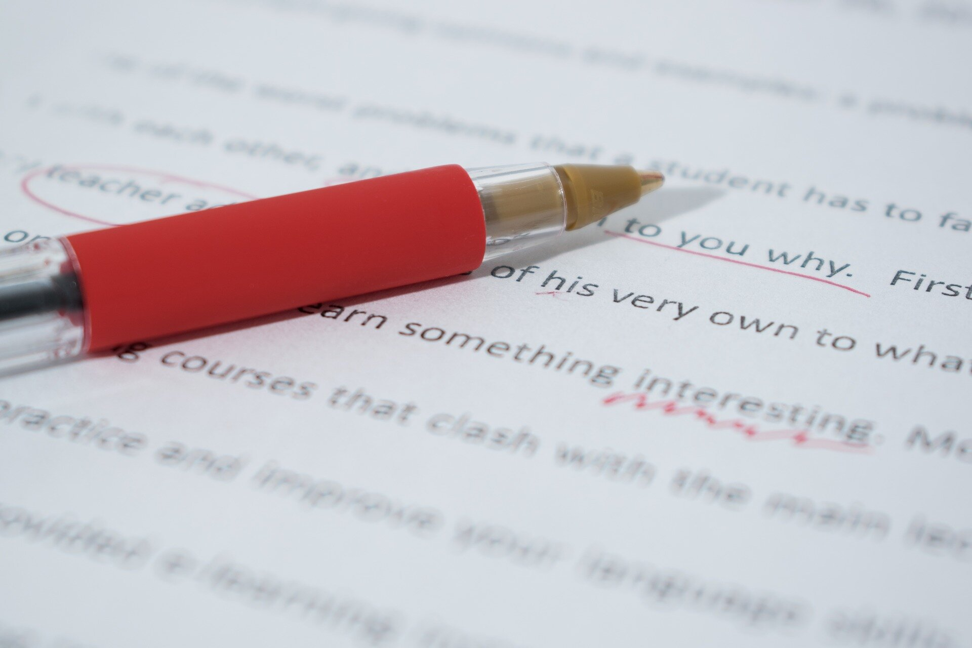 a red pen laying on an edited paper.