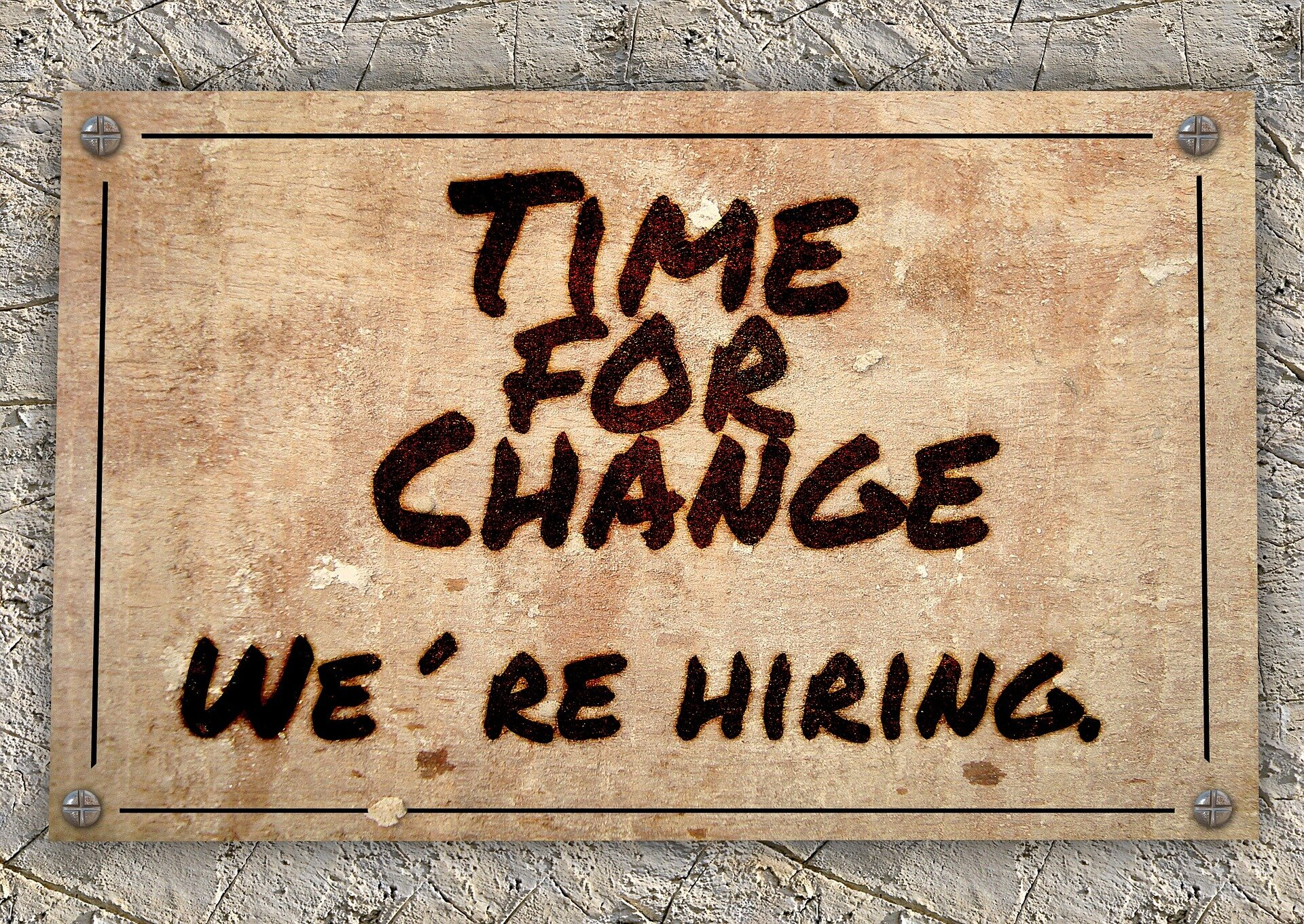 "a wooden sign that reads, ""Time for a change, we're hiring"""