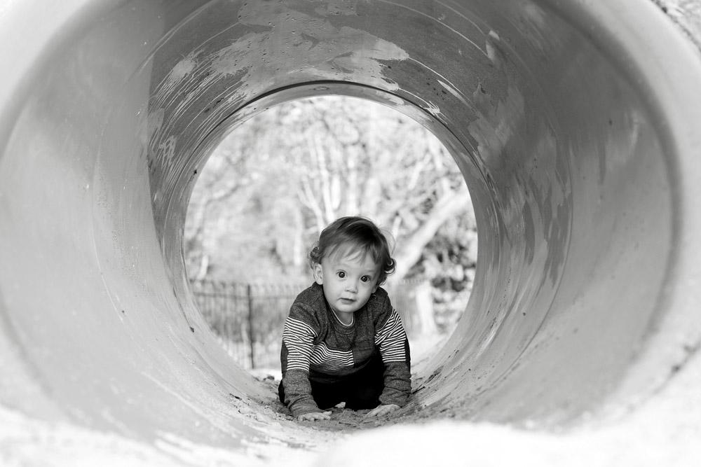 Boy in a playground tunnel