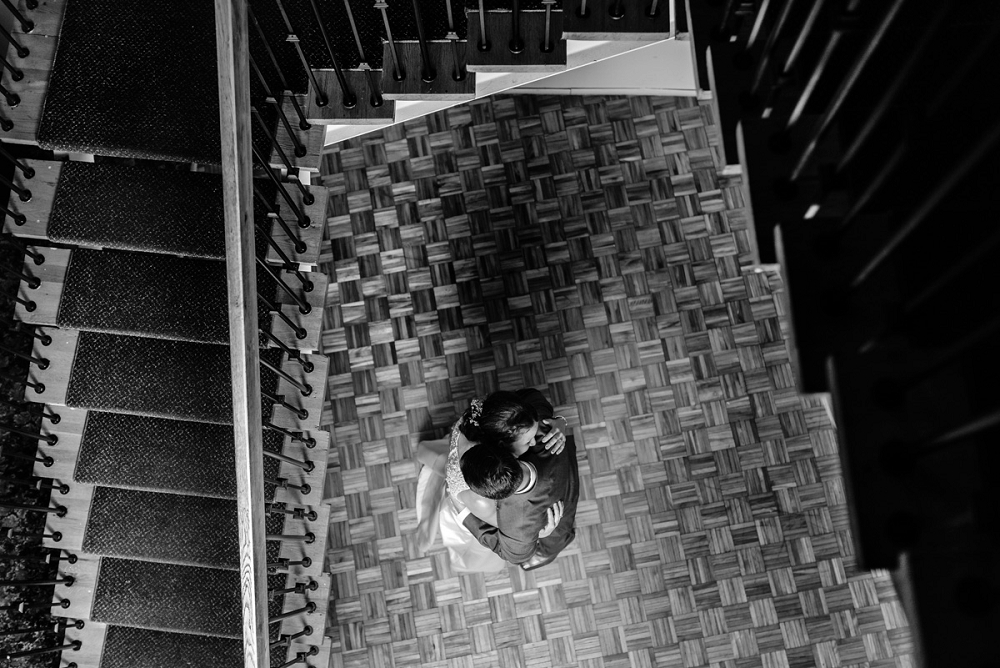 black and white photo of a married couple at the bottom of the stairs