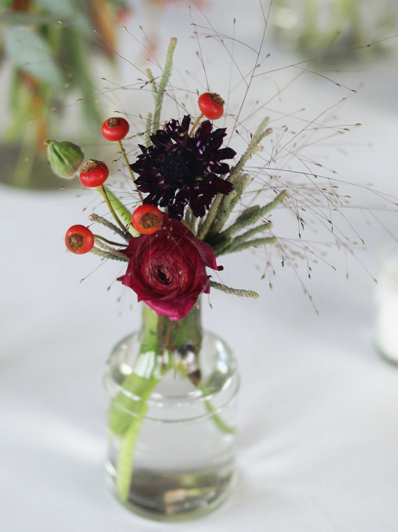 Oreonta house woodstock wedding bud vase with burgundy ranunculous, , grey brunia, red berries and red rosehips and wildflowers rosehip social rosehip floral wild grass.jpg