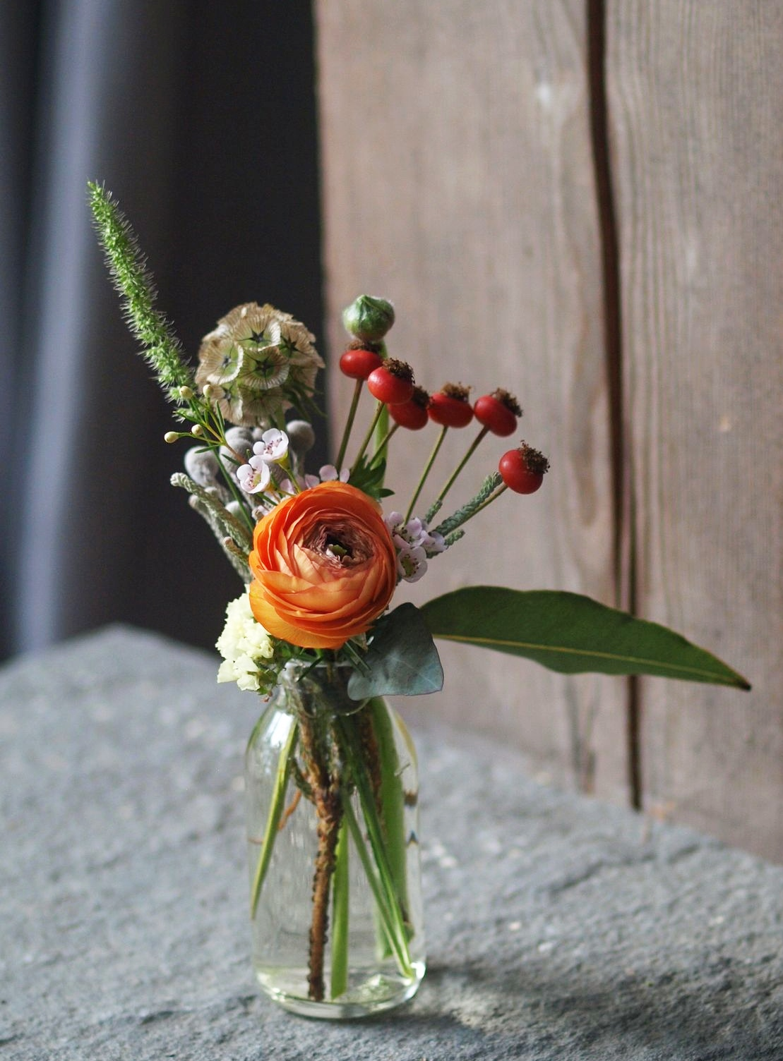 Oreonta house woodstock wedding bud vase with orange ranunculous, lambs ears, grey brunia, red berries and red rosehips and wildflowers rosehip social rosehip floral pink wax flowers.jpg