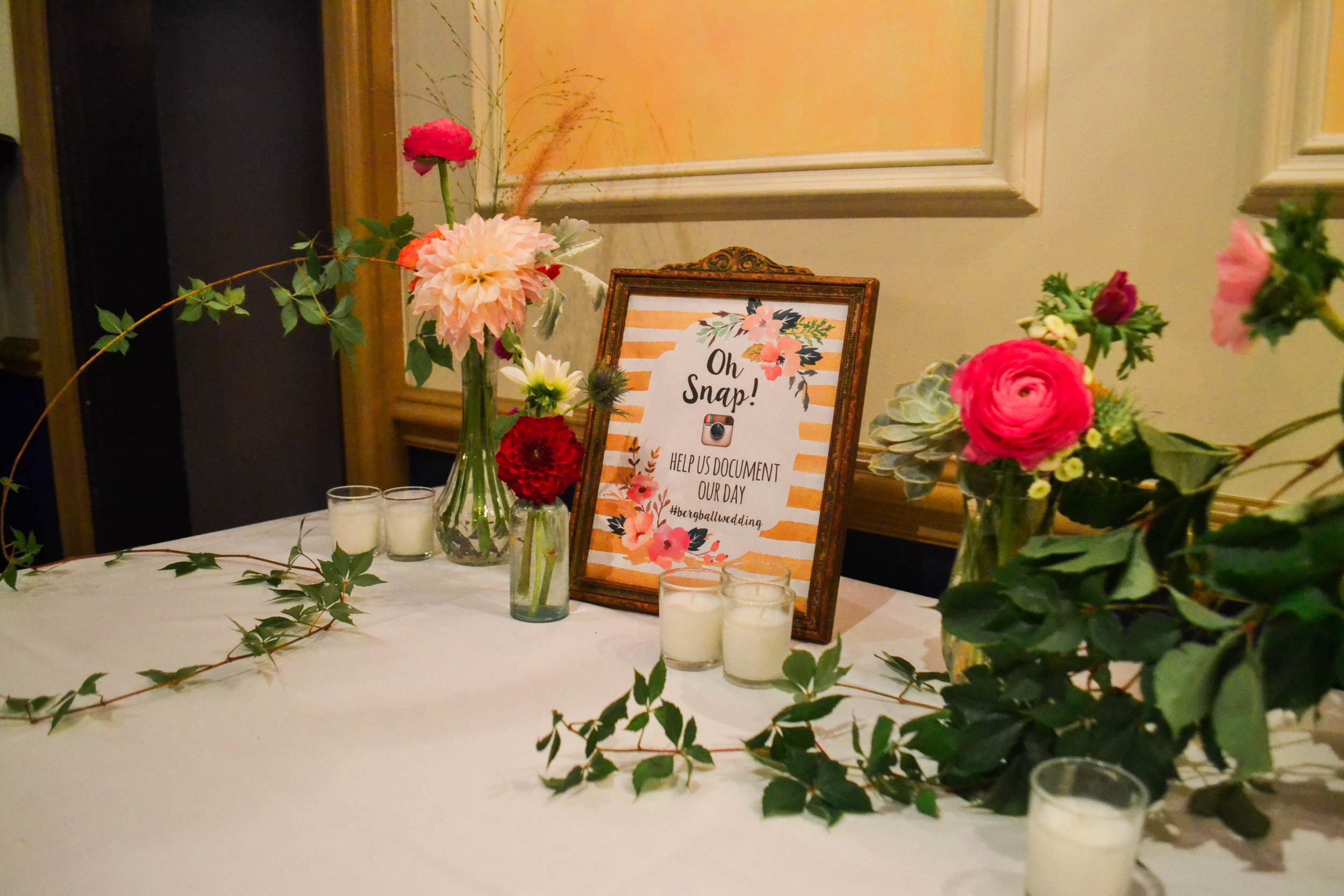 Colorful and romantic flower place card table flowers in bud vase bottle. Catskills wedding. August.
