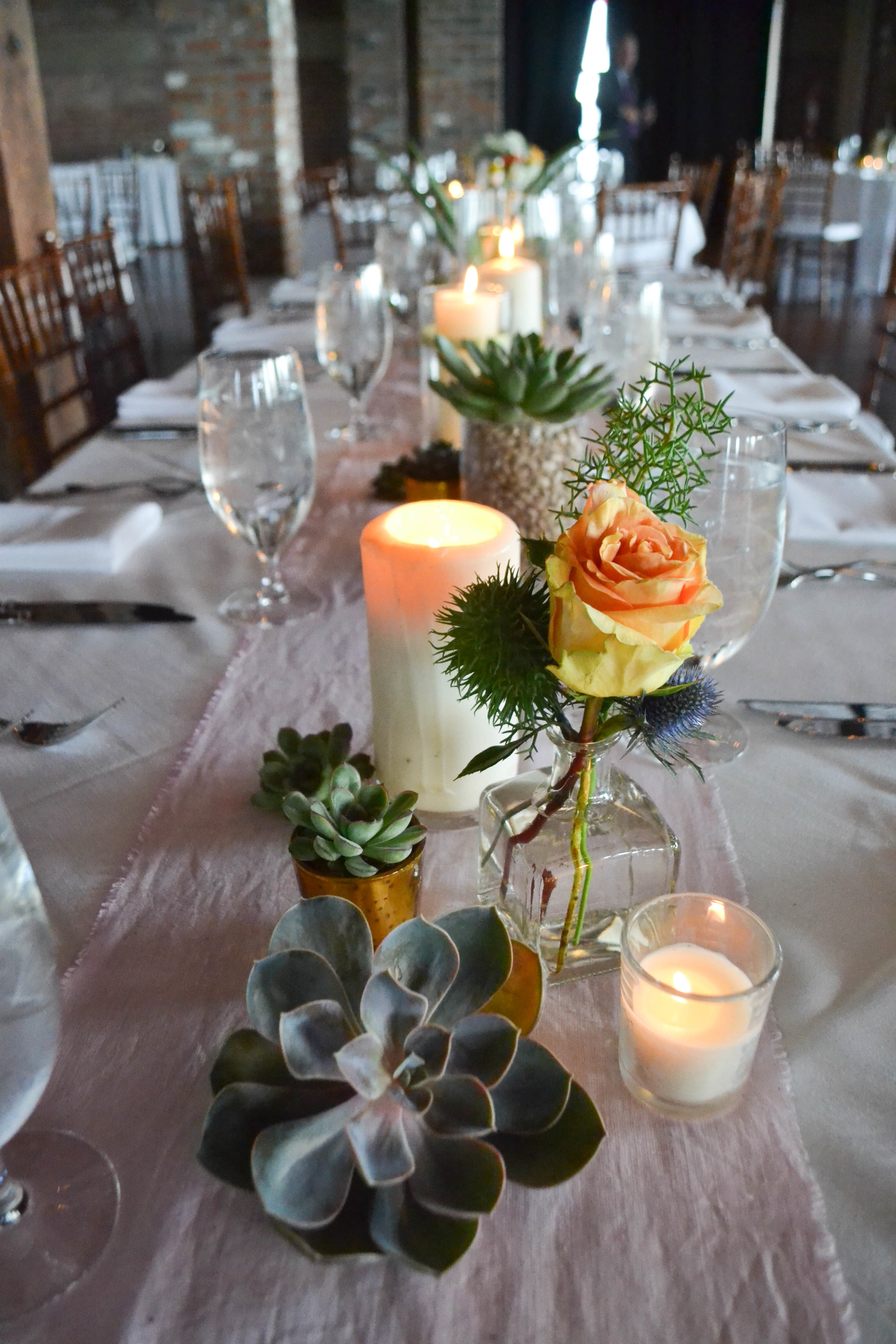 Liberty Warehouse Southwest Succulent Mexican wedding. Rosehip Floral BrooklynOrange, pink, white and slate blue centerpieces with succulents and candles.