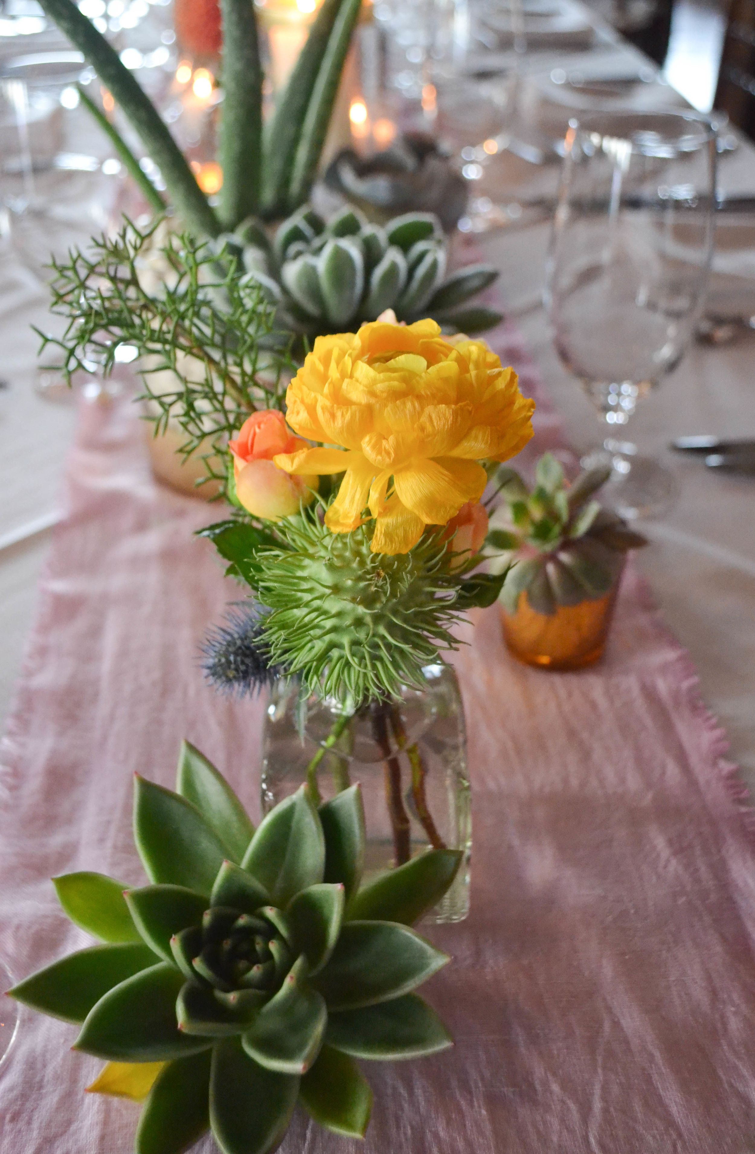 Liberty Warehouse Southwest Succulent Mexican weddingOrange, pink, white and slate blue centerpieces with succulents and candles.