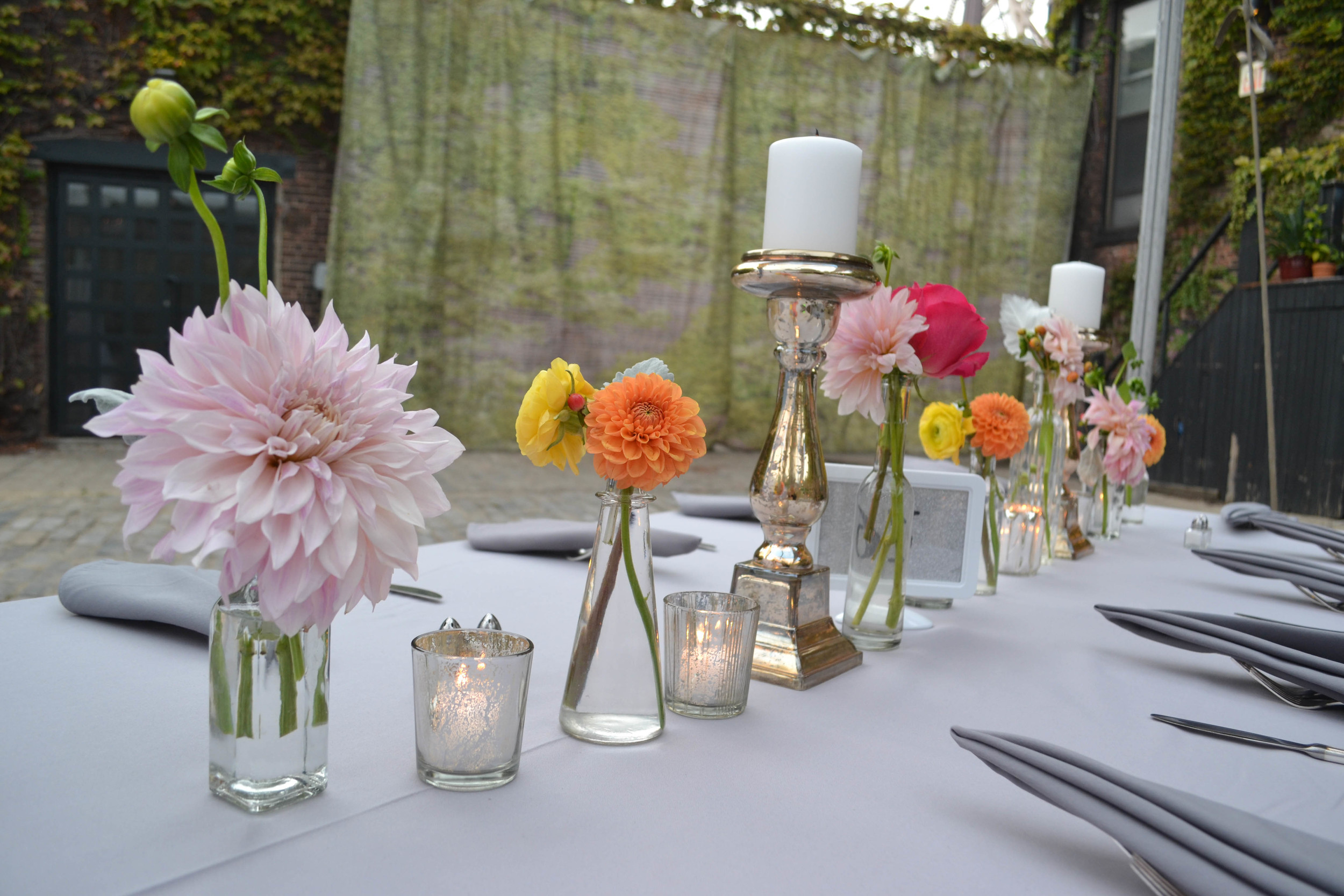 Peach toned dahlias and garden rose centerpiece with silvery greens and raspberry pink accent flowers. Foundry LIC wedding. Rosehip Brooklyn