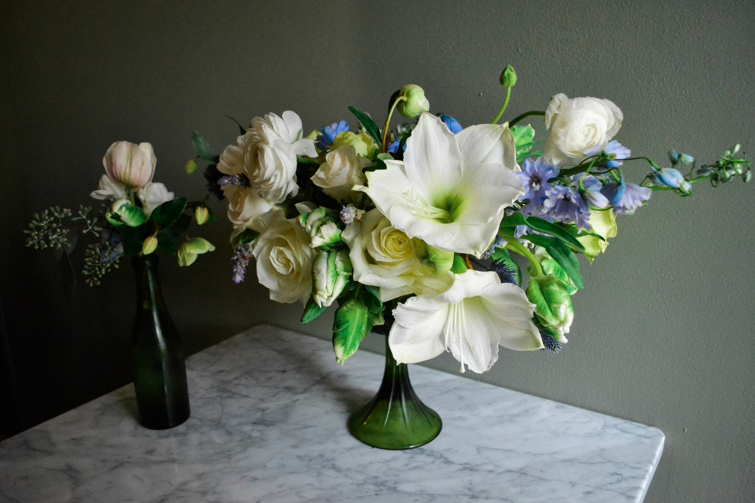 Green and white compote centerpiece flower arrangement with blue and lavender accents. Baby Shower flowers for Garden Collage. Amaryllis, parrot tulip, jade green roses, ranunculous, lavender.