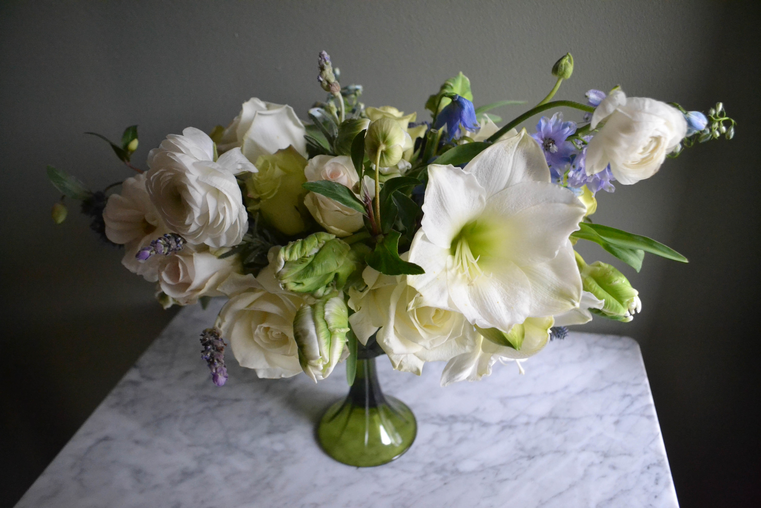 Green and white compote centerpiece flower arrangement with blue and lavender accents. Baby Shower flowers for Garden Collage.