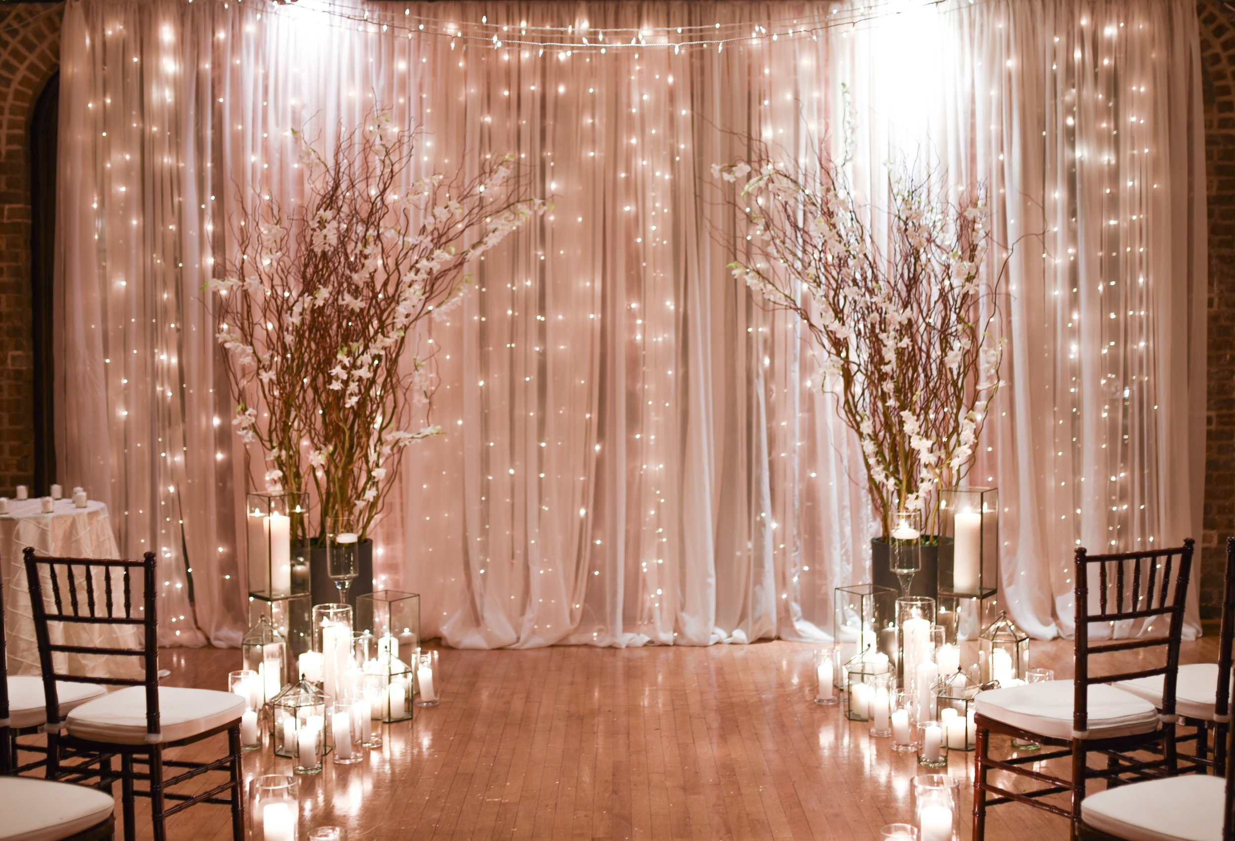 A glowing ceremony backdrop of curly willow, white orchids, and staggered candles