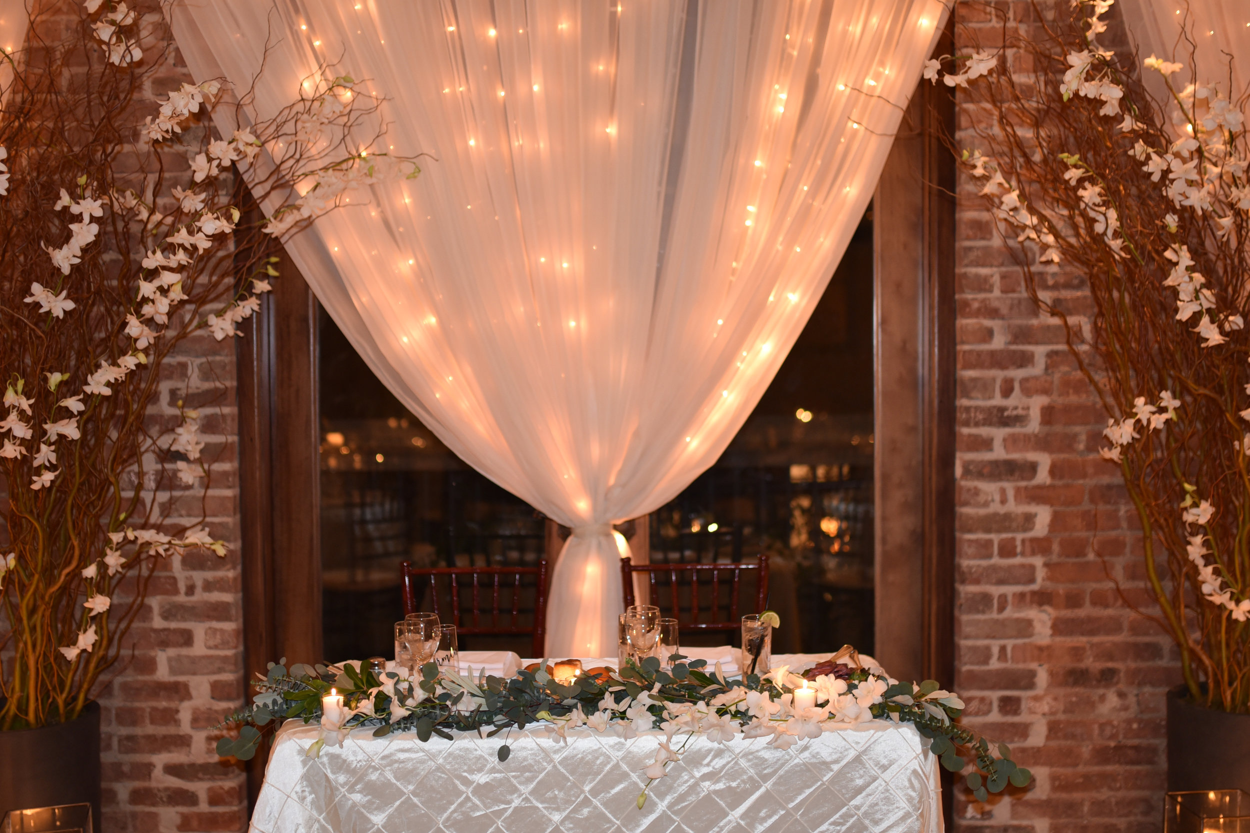 The eucalyptus garland at the sweetheart table is radiantly lit under curly willow and white orchids