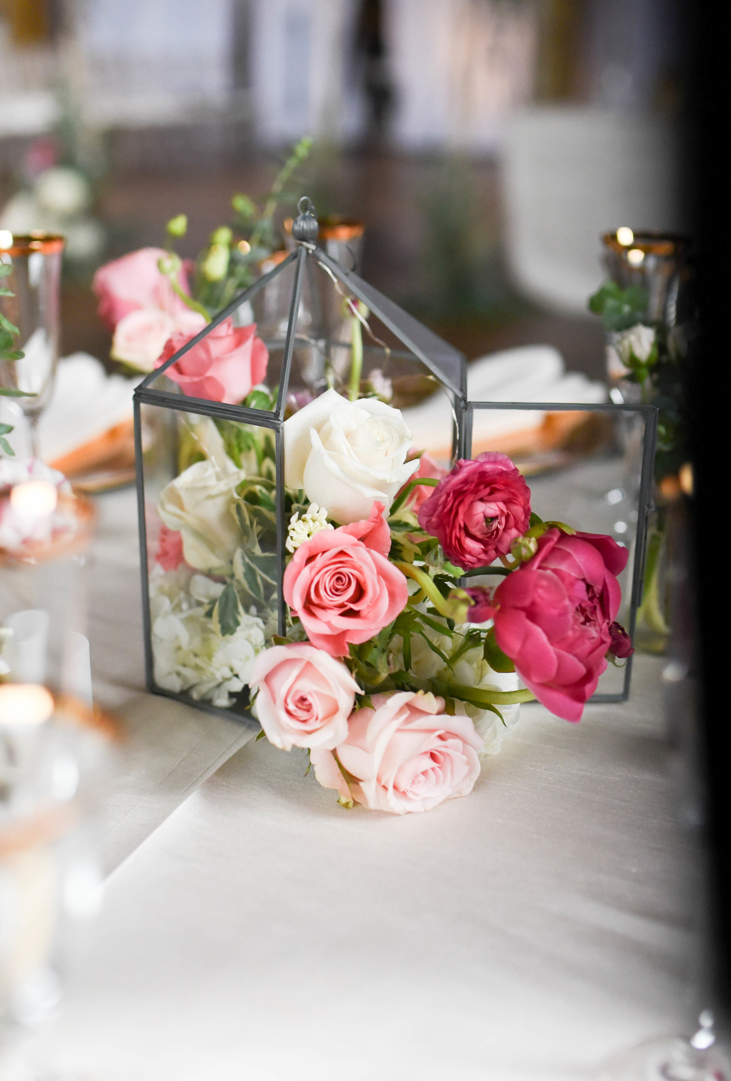 Roses, ranunculus and peonies pour from this lantern