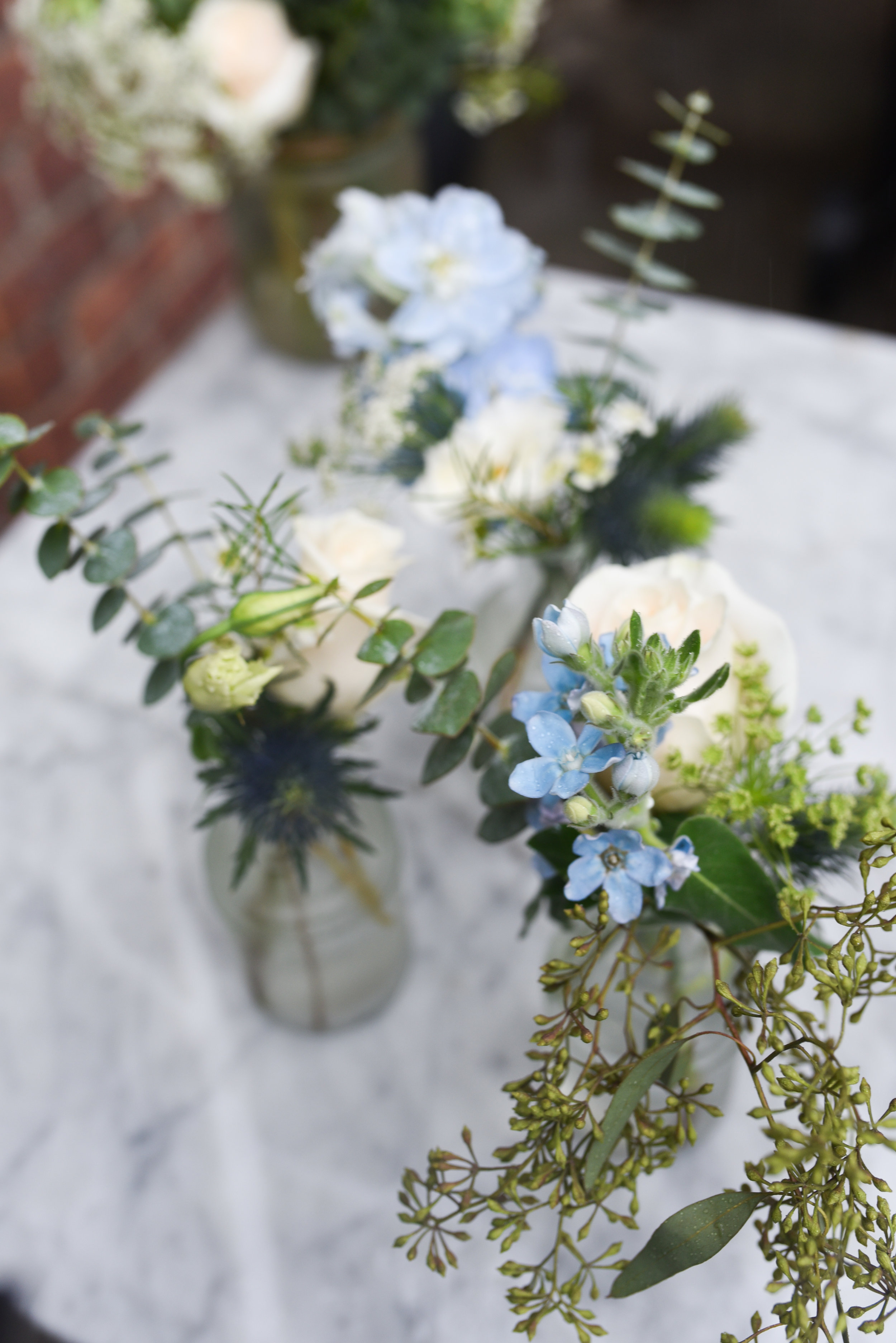 Clear bud vases with blue and white flowers look like a natural English garden at this Brooklyn wedding