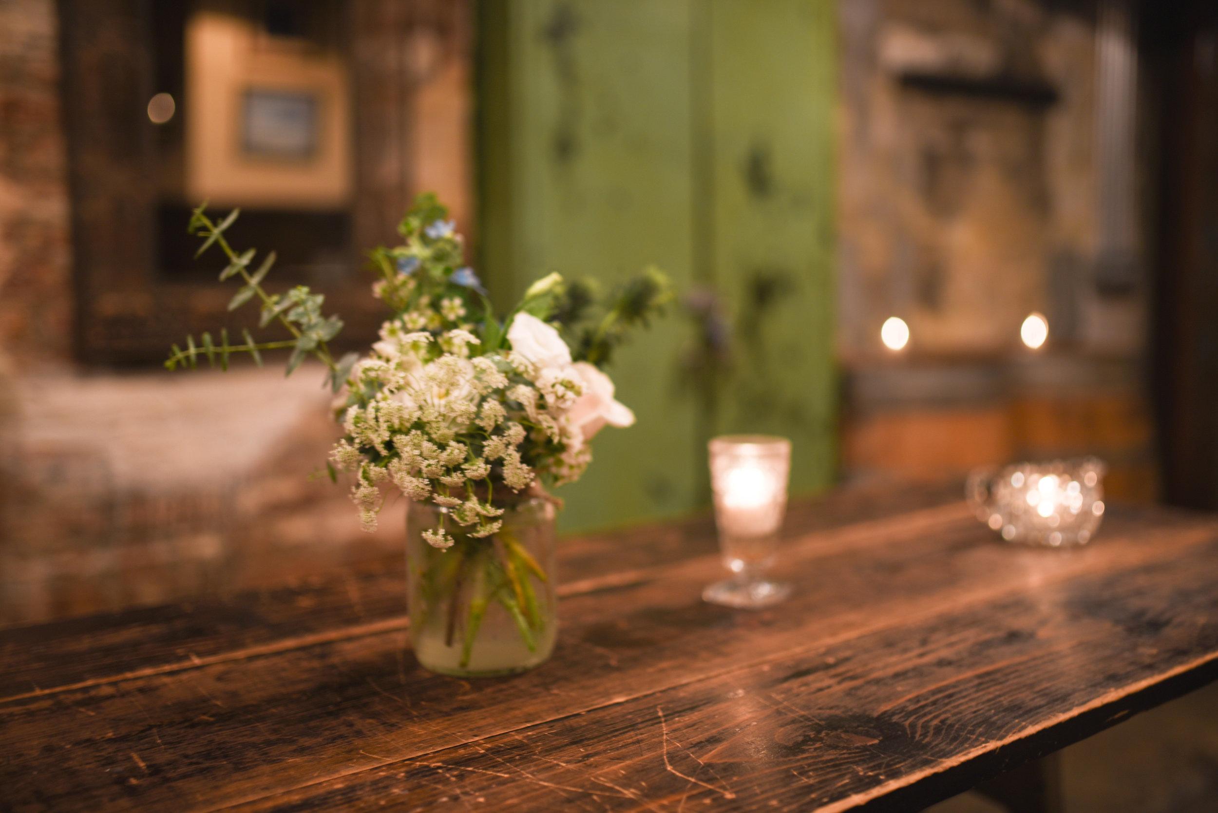 Flower arrangements in mason jars at this Brooklyn wedding reception