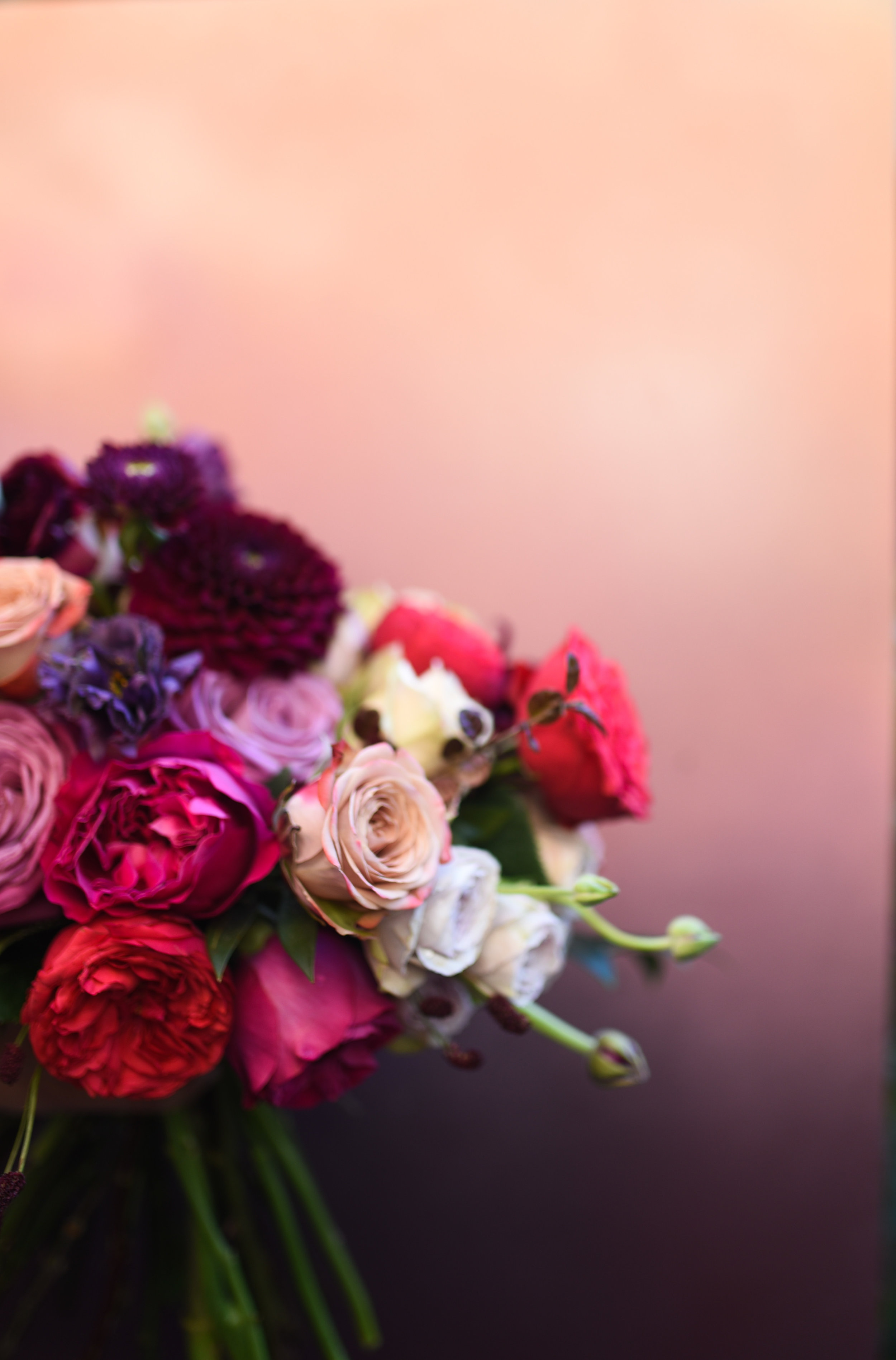 This view showcases the colors and varieties of tea and garden roses in this hand-tied bouquet